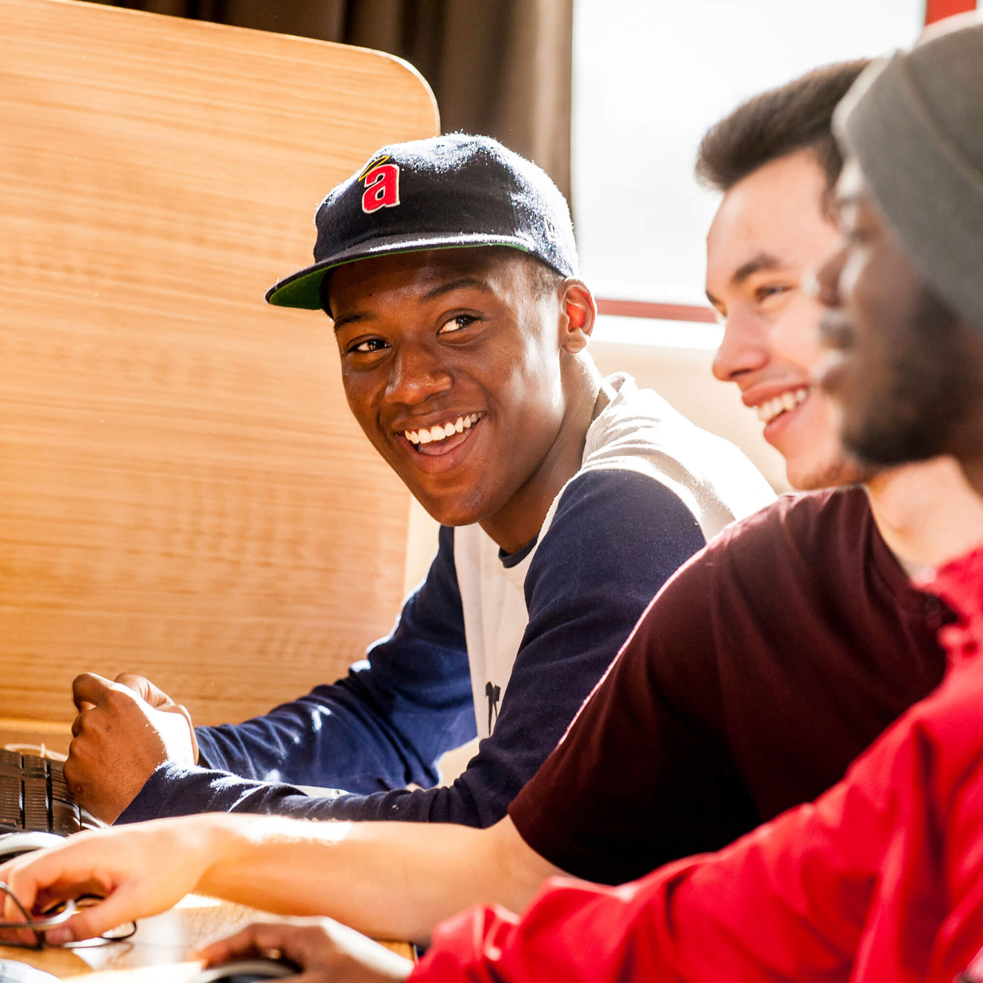 Students smiling and talking at a computer desk