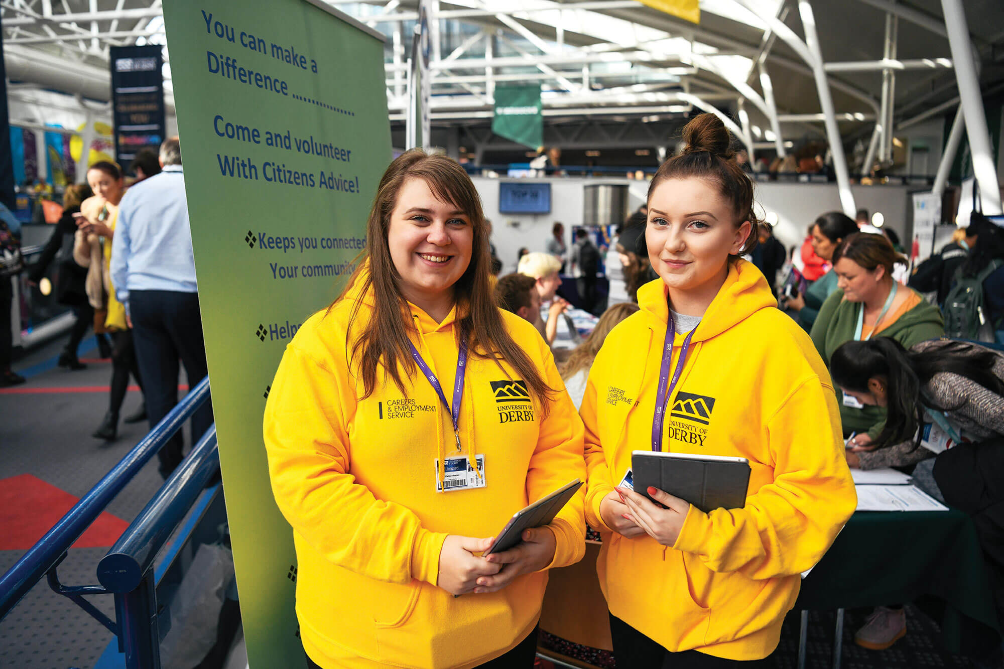Two students wearing yellow hoodies and holding iPads at a Volunteering Fair in the atrium