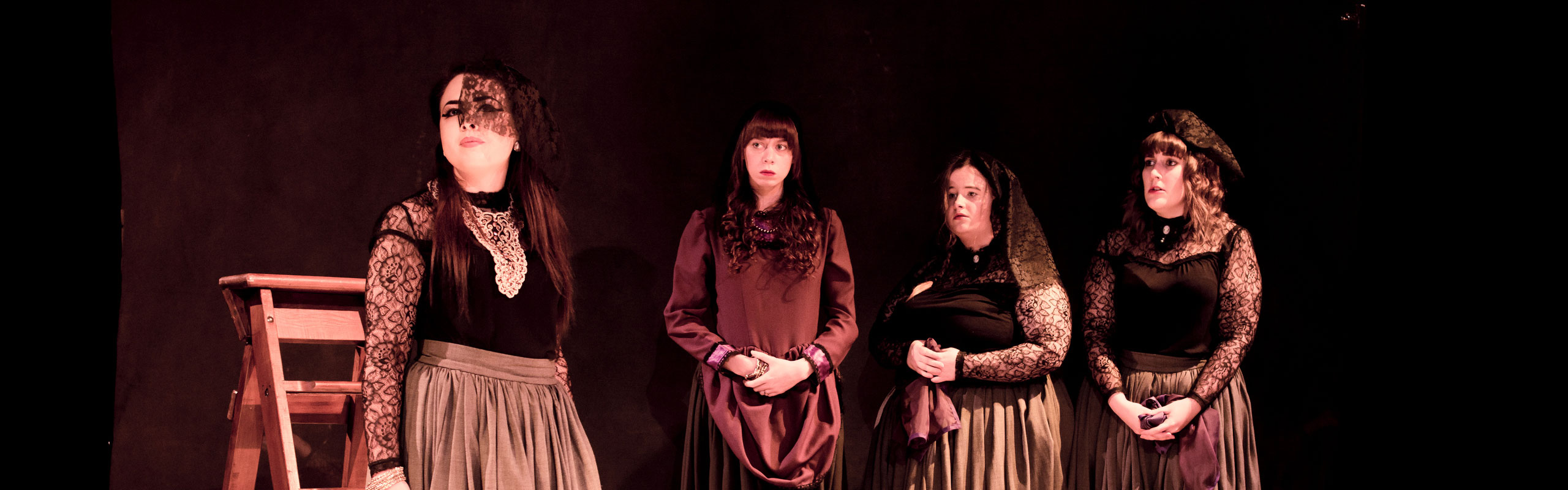 Four students standing acting during performance at Derby Theatre