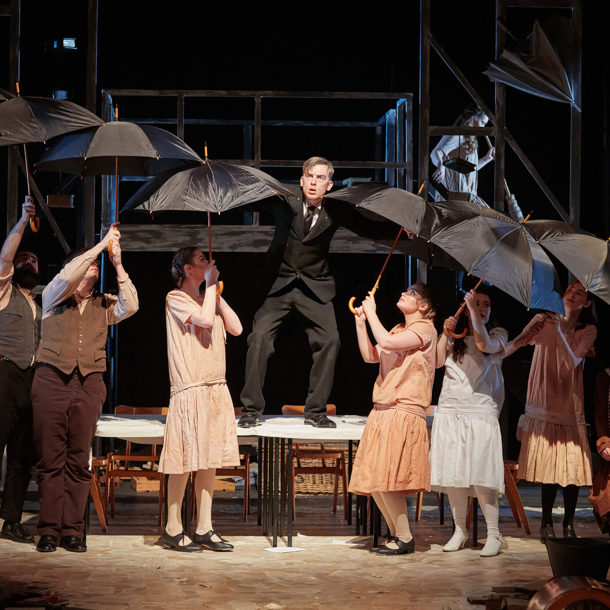 Theatre students holding umbrellas whilst performing on stage at Derby Theatre