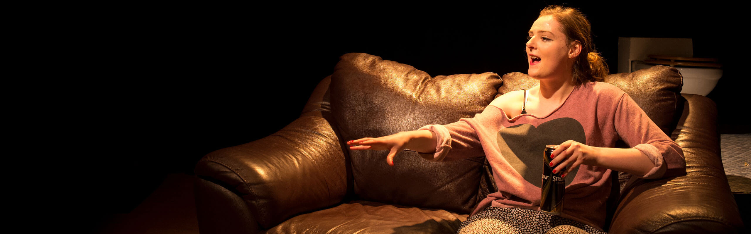 Student sitting on sofa acting during performance at Derby Theatre