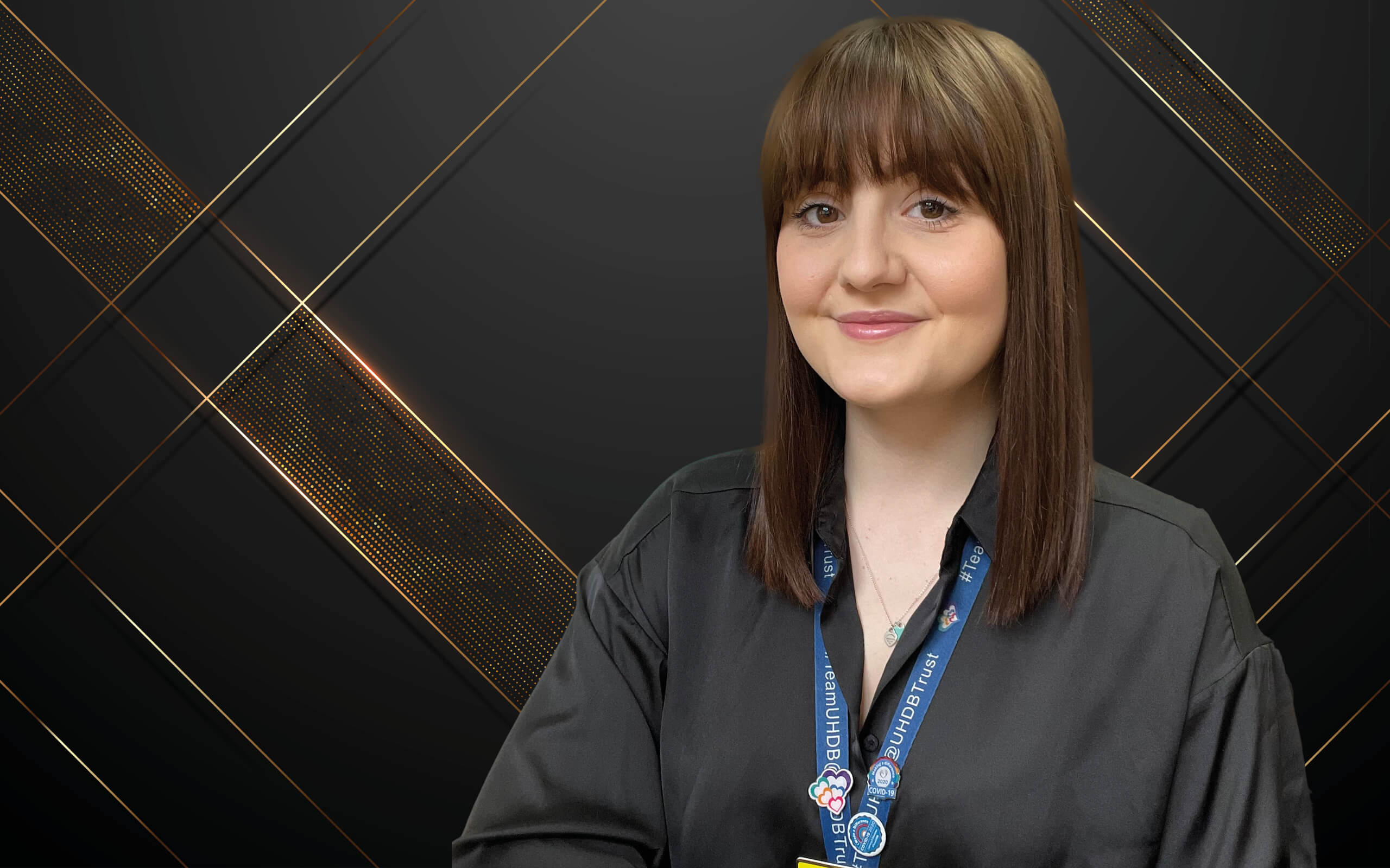 Sian Brown standing against a black and brown background.