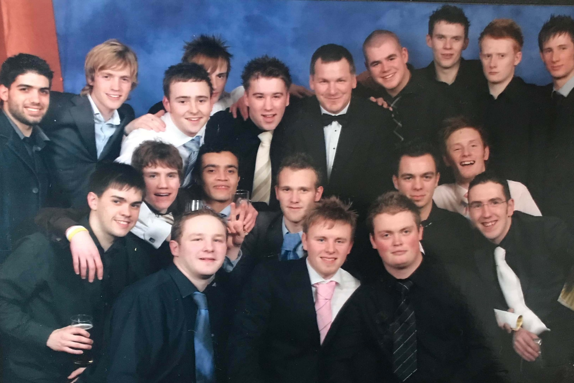 A group of university students wearing shirts and ties with TV presenter Ray Stubbs, wearing a dinner jacket, all posing for and smiling at the camera.