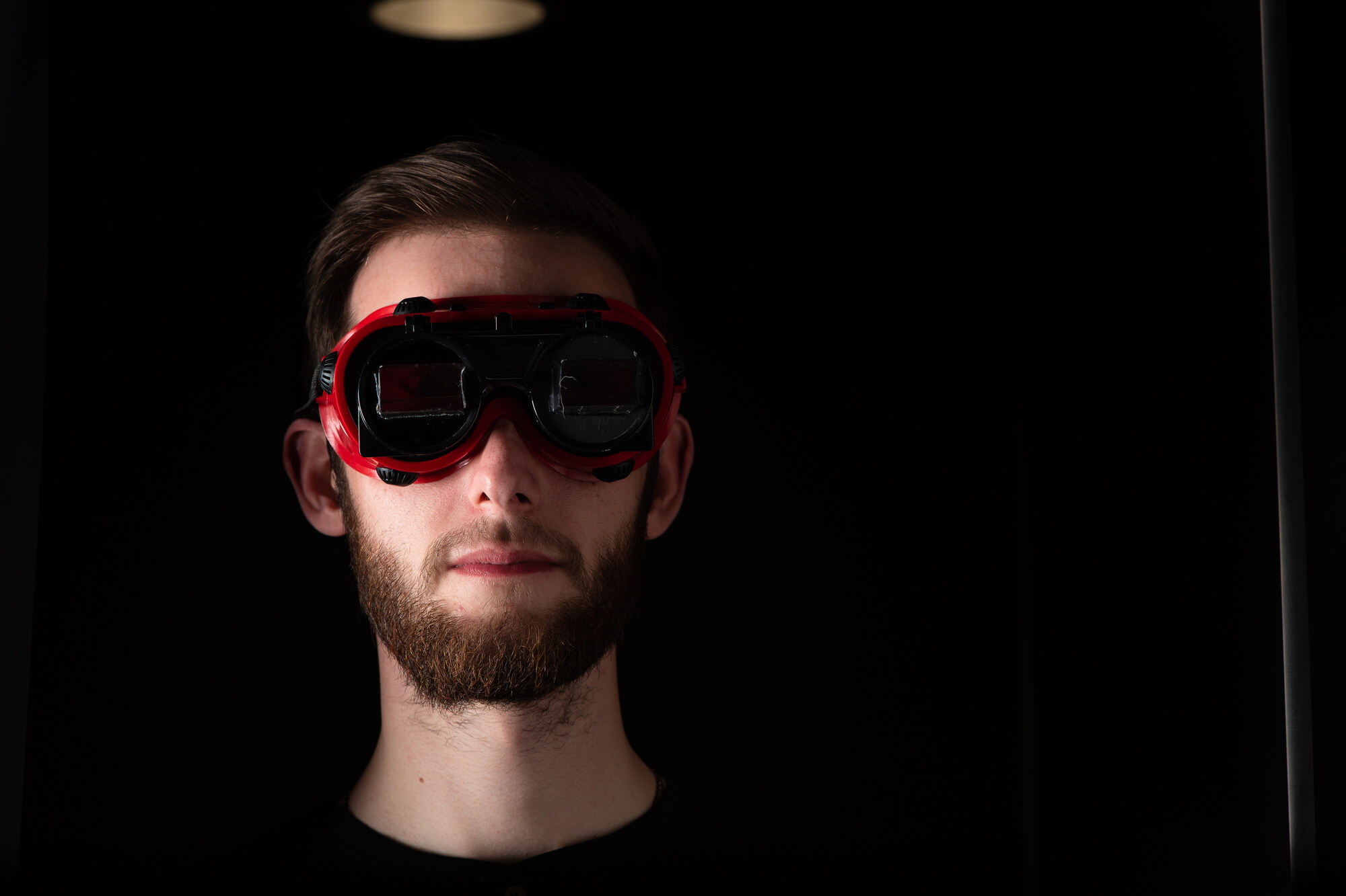 A male student using the eye tracking equipment in a dark room