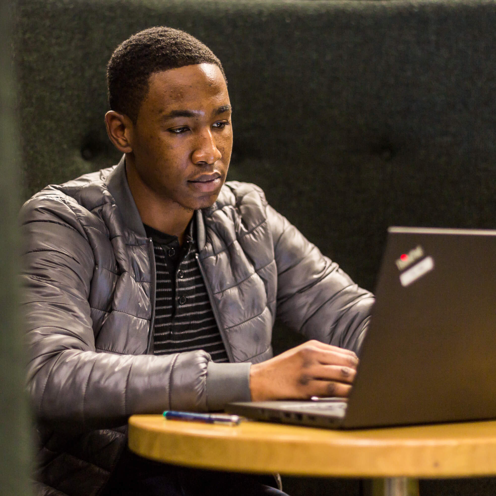 A student sitting at a desk, looking at a laptop