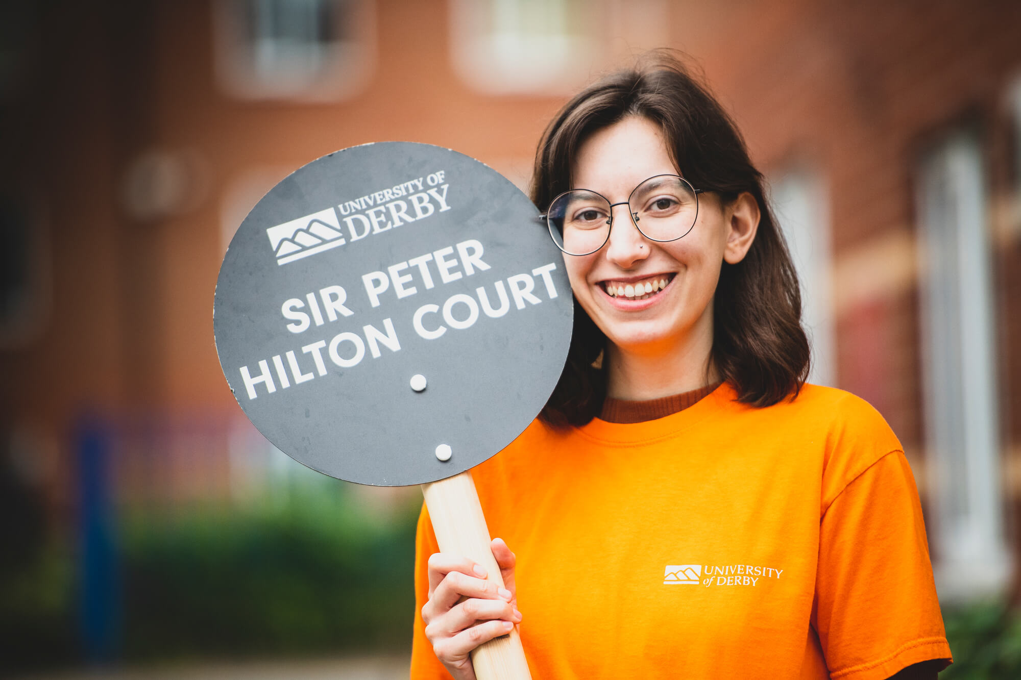 A smiling female Student Ambassador holding a sir peter hilton accommodation sign on an Open Day