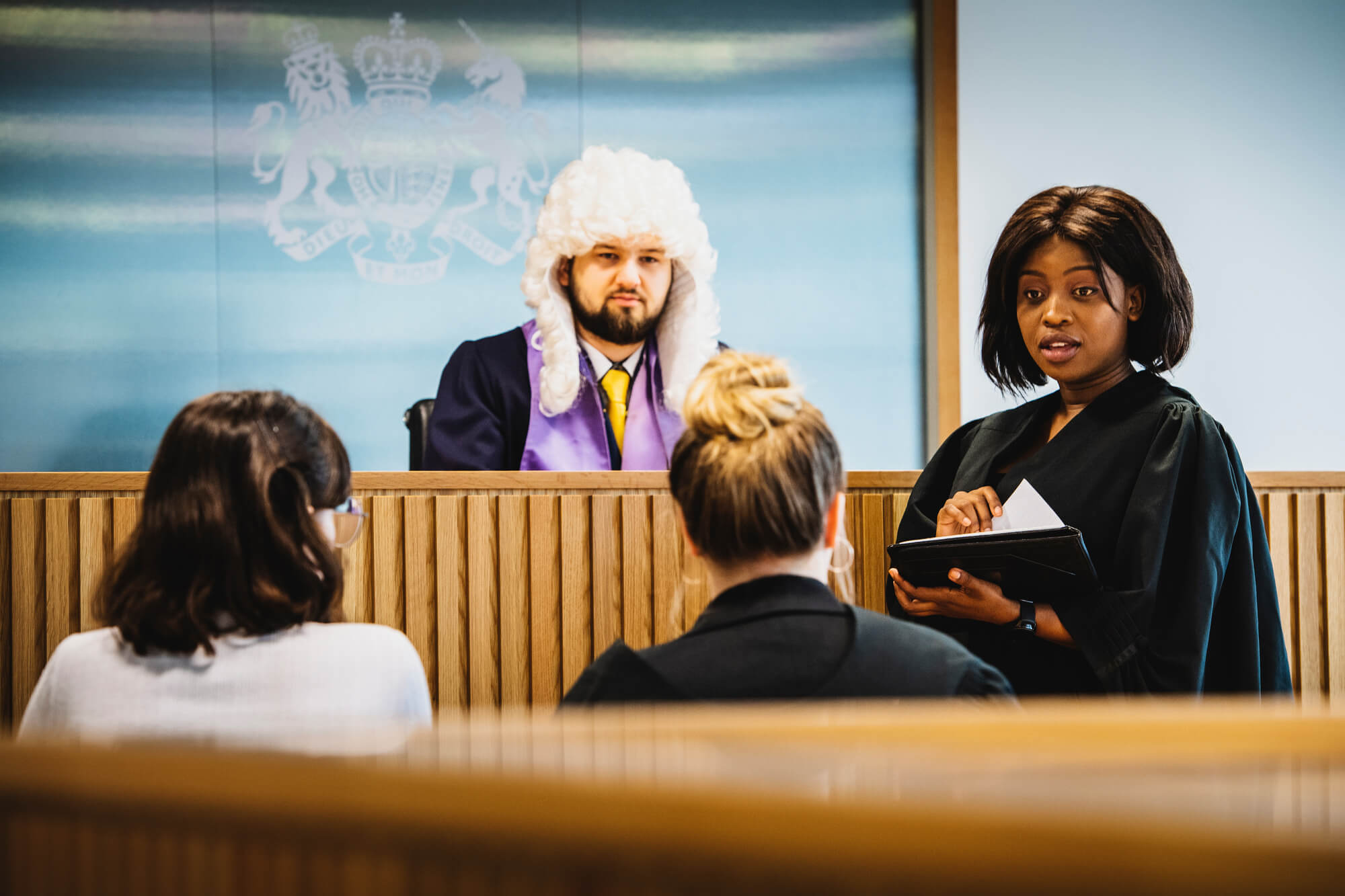 male and female students taking part in a mock trail in our law court, one student is dressed as judge, one as a solicitor and the rest the jury
