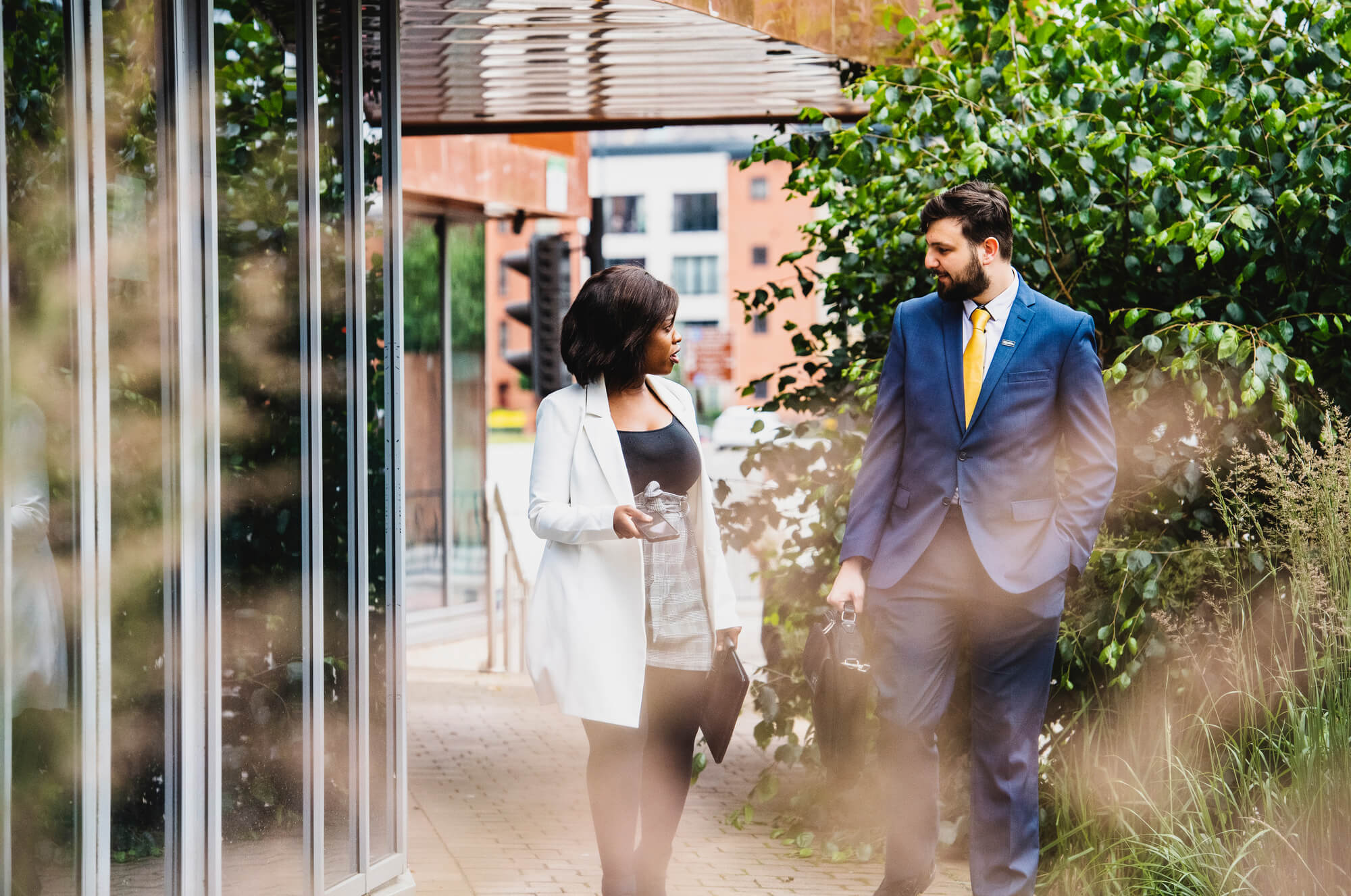 A female and Male student dressed in business wear, walking and talking outside a university building