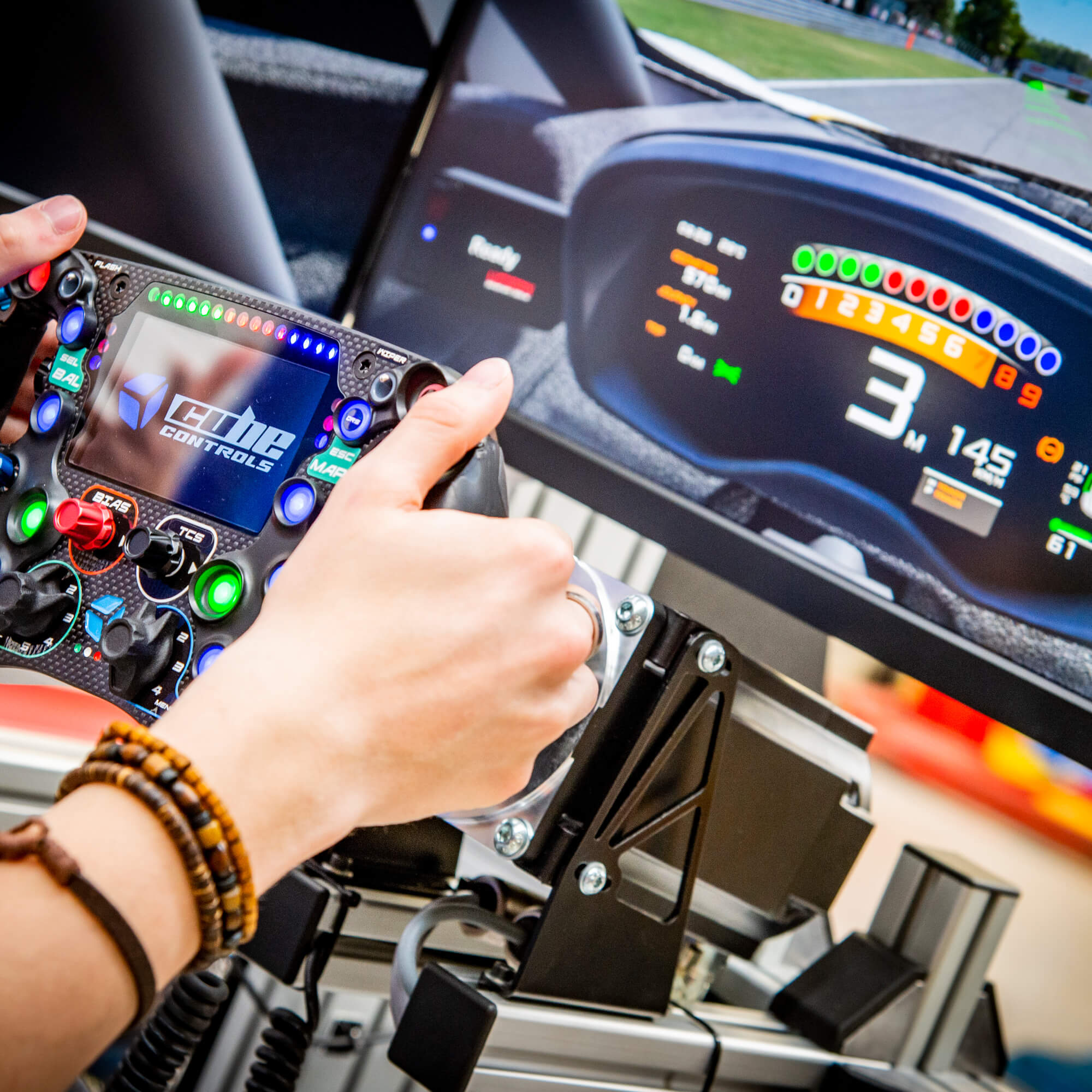 A close up image of a students hands and the dashboard whilst operating the electric cars