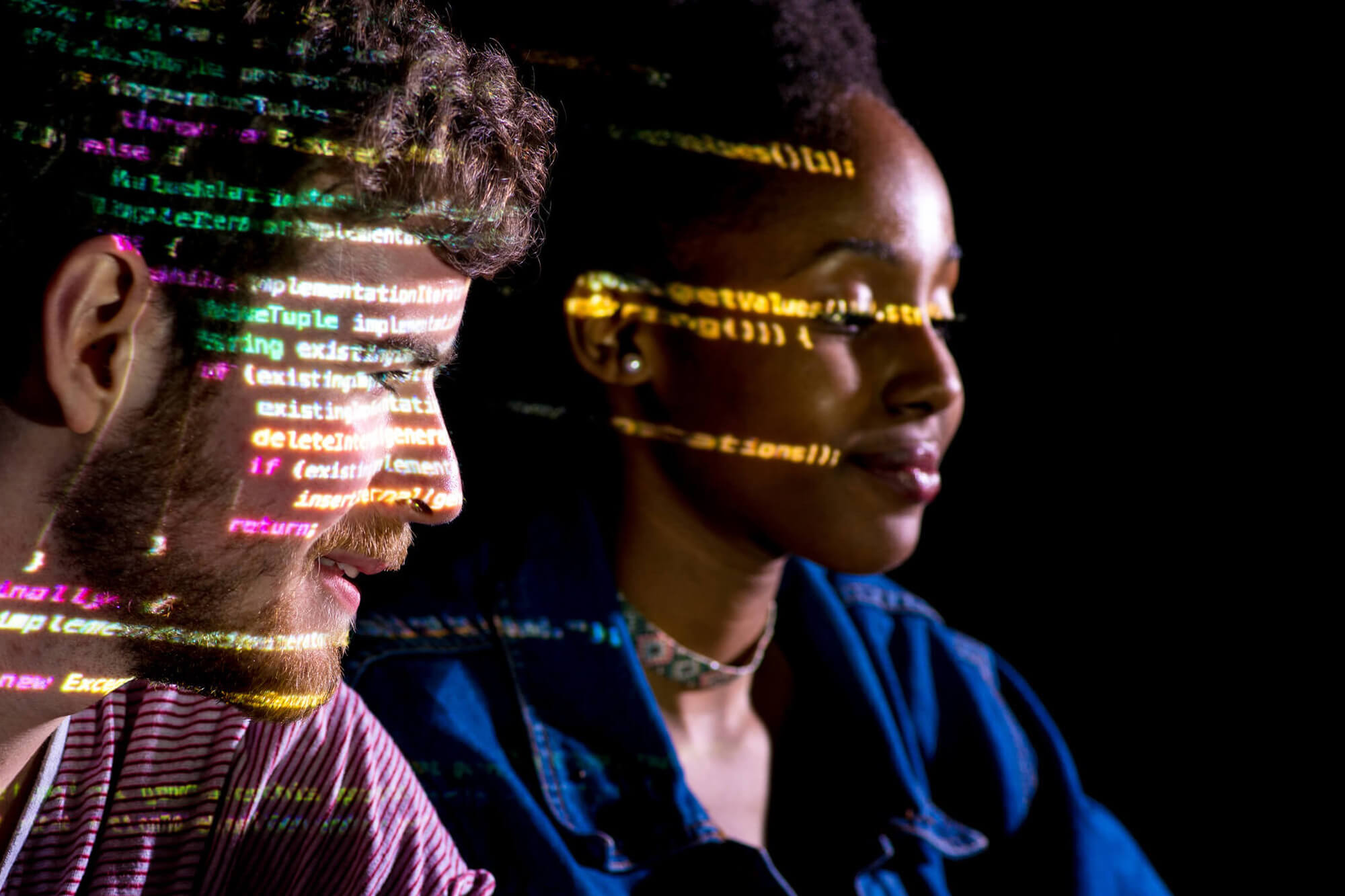 A female and male student sat working in a dark room, with a projection of their computer screen reflecting on their faces showing mathematical equations