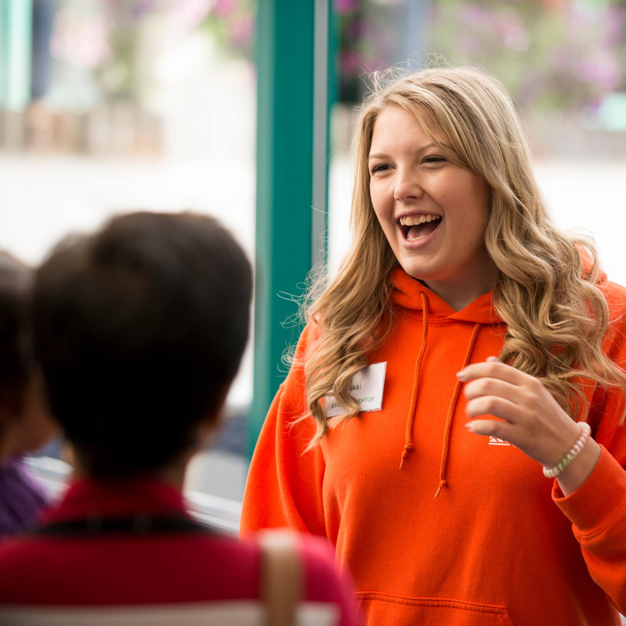 A student ambassador smiling and talking to visitors