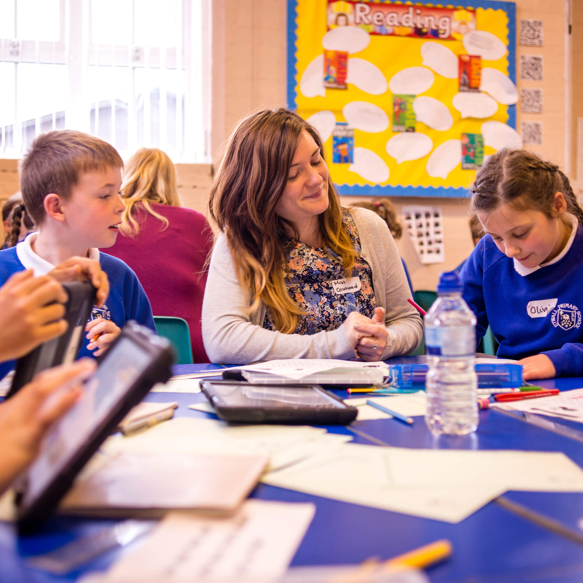 Student teacher sitting at a table with primary school pupils