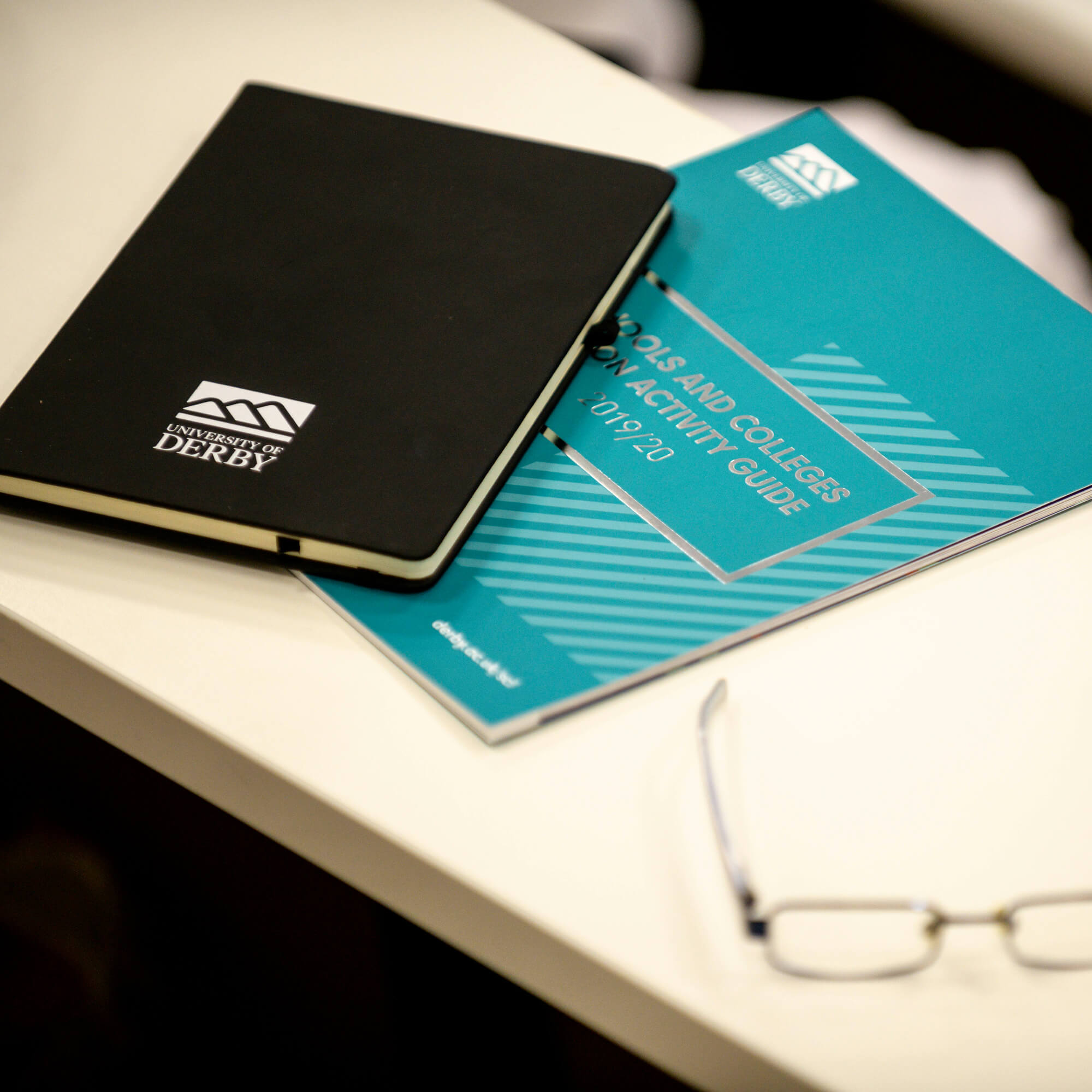 A desk with a copy of the Schools and Colleges Liaison Brochure, a notepad and a pair of glasses