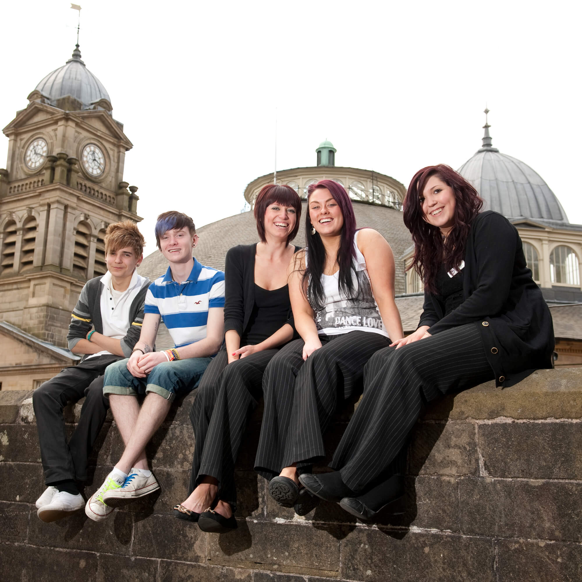 Buxton & Leek College students sitting on a wall in Buxton