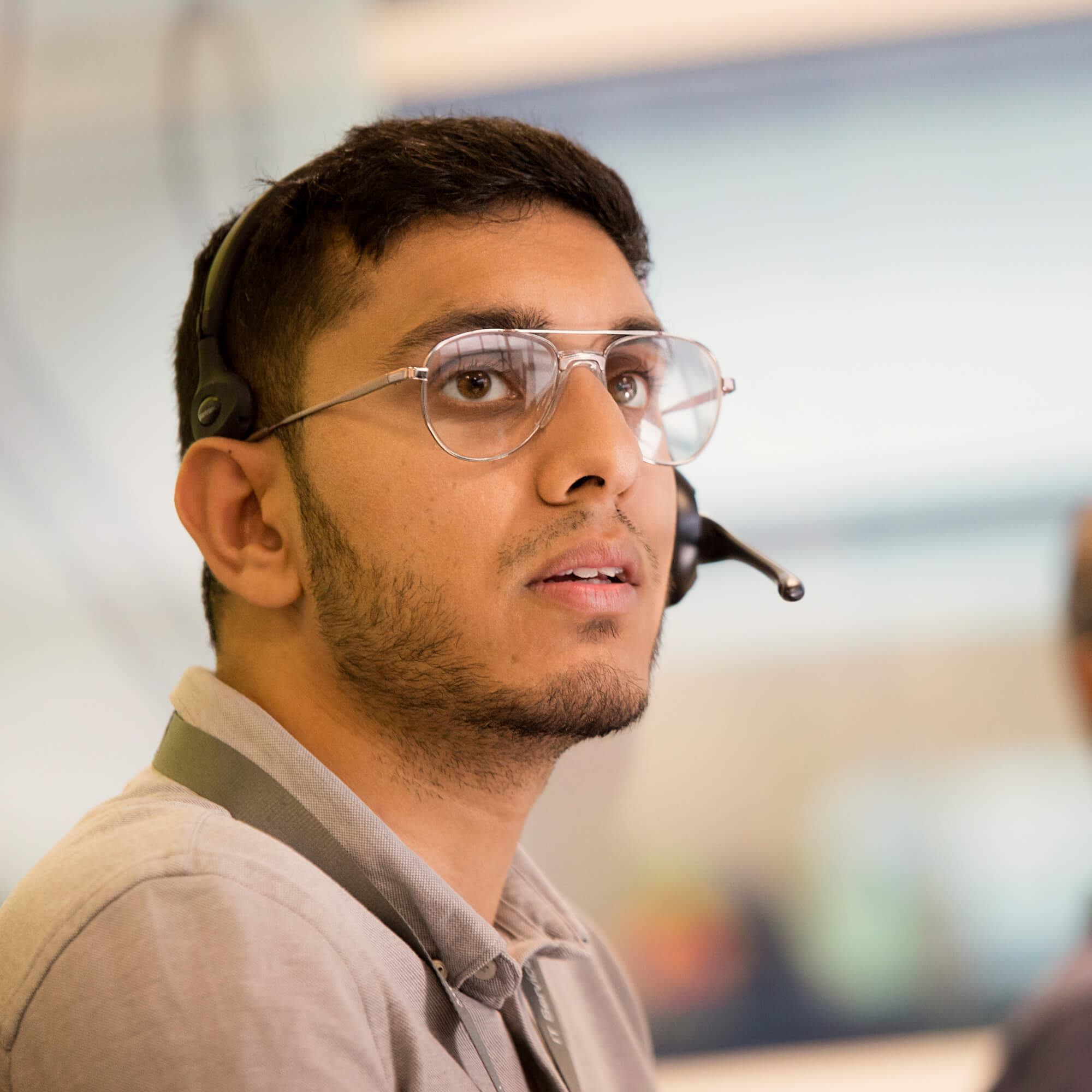 A young man with a phone headset on in the IT Service Centre.
