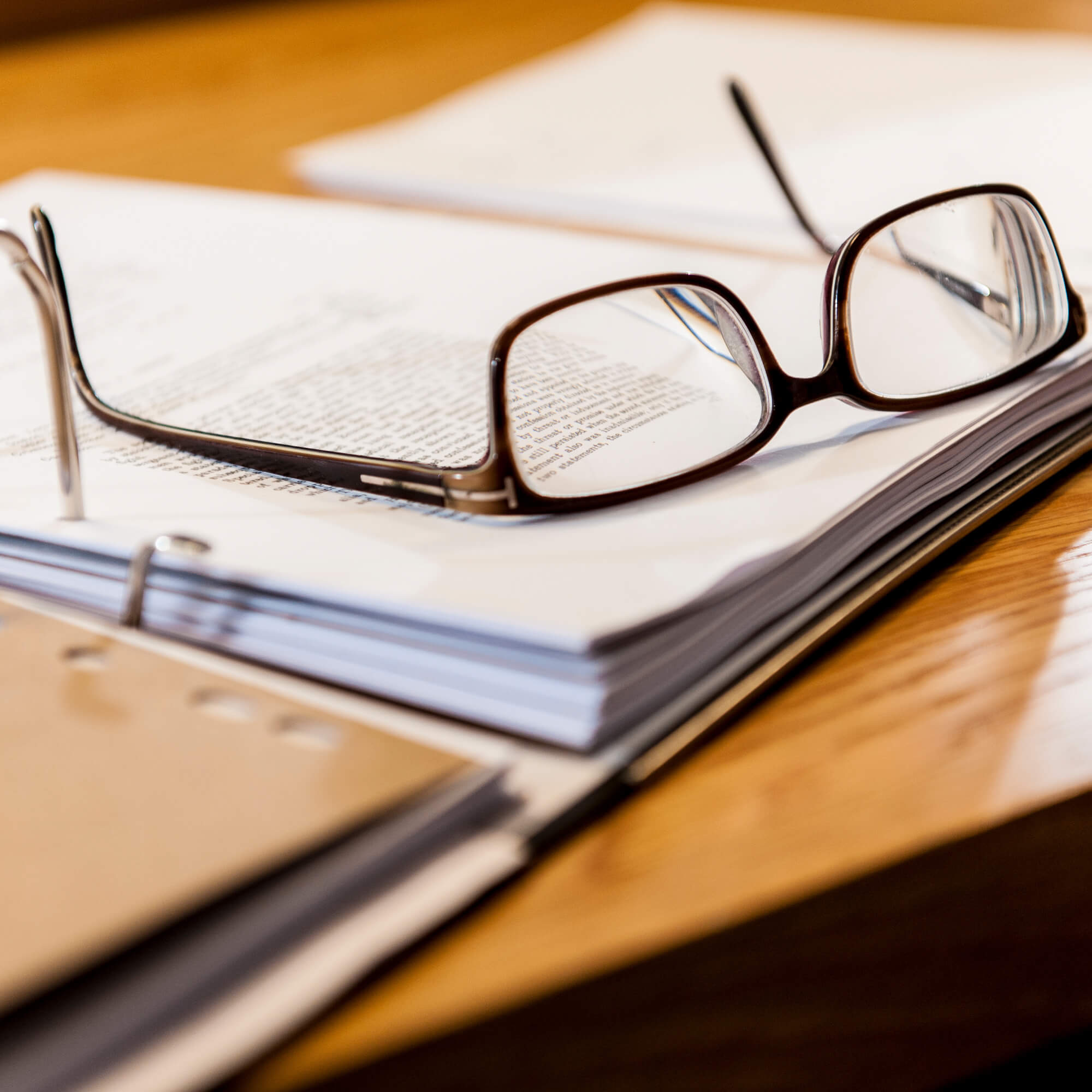 Eye glasses on top of an open binder of paperwork.