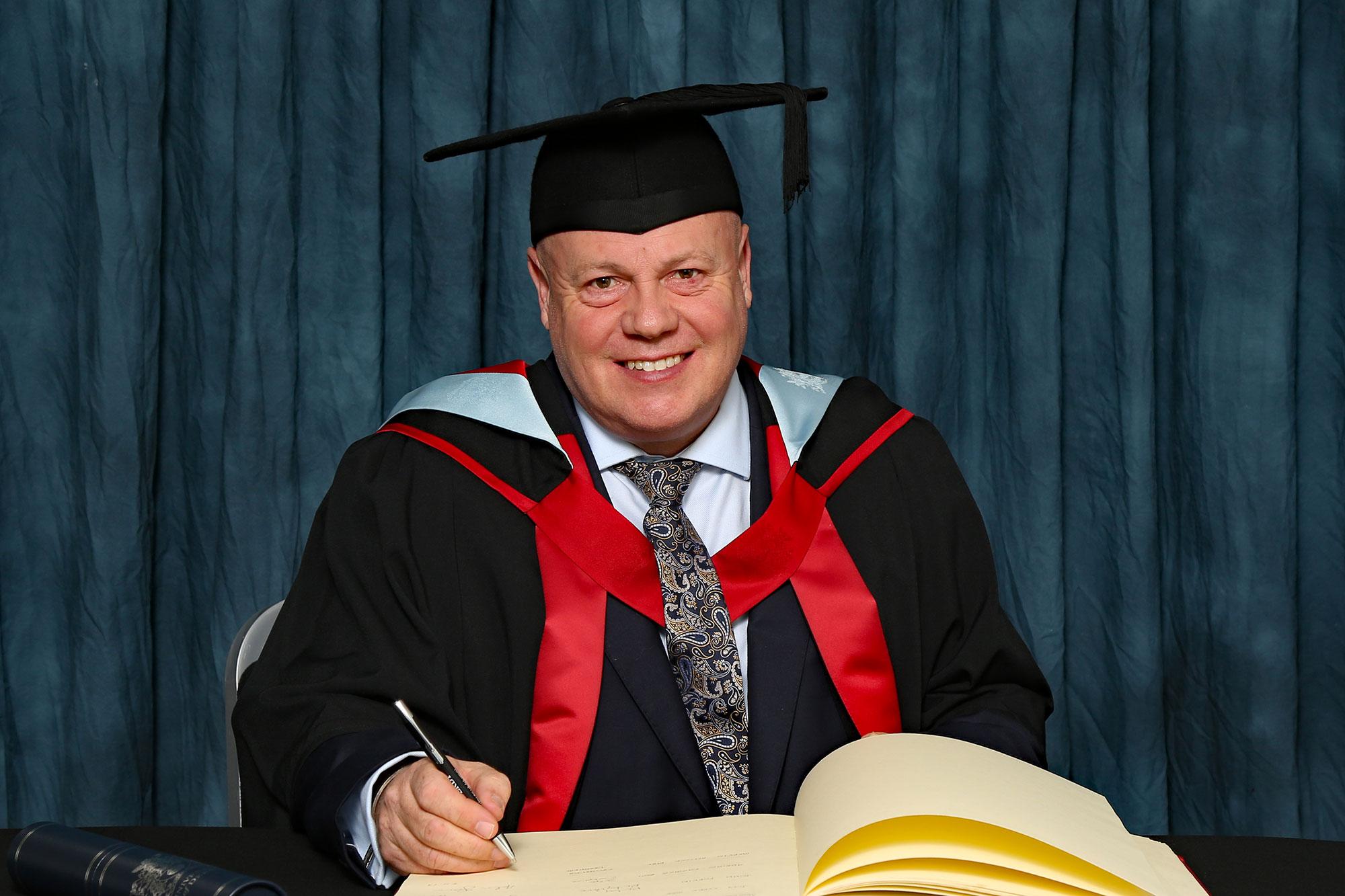 Mervyn Allcock MBE receiving his honorary degree, HonMUniv, November 2019