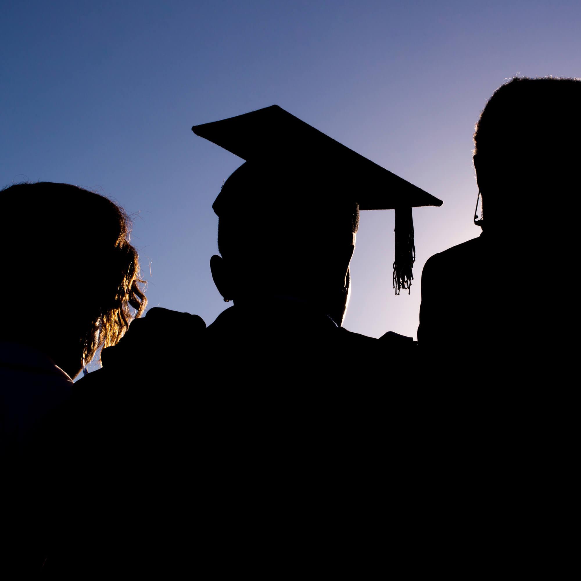 A silhouette of a graduate wearing a graduation cap
