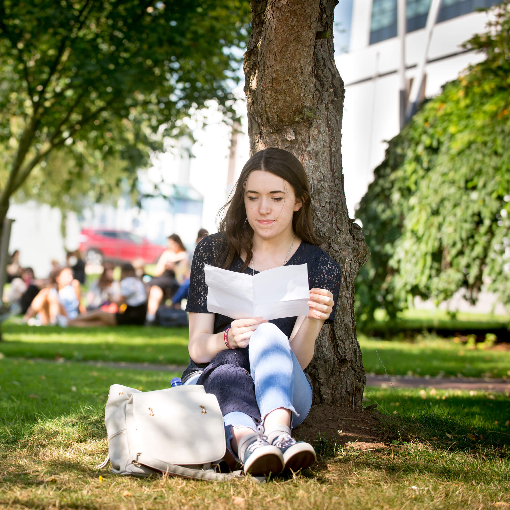 a student sat under a tree reading