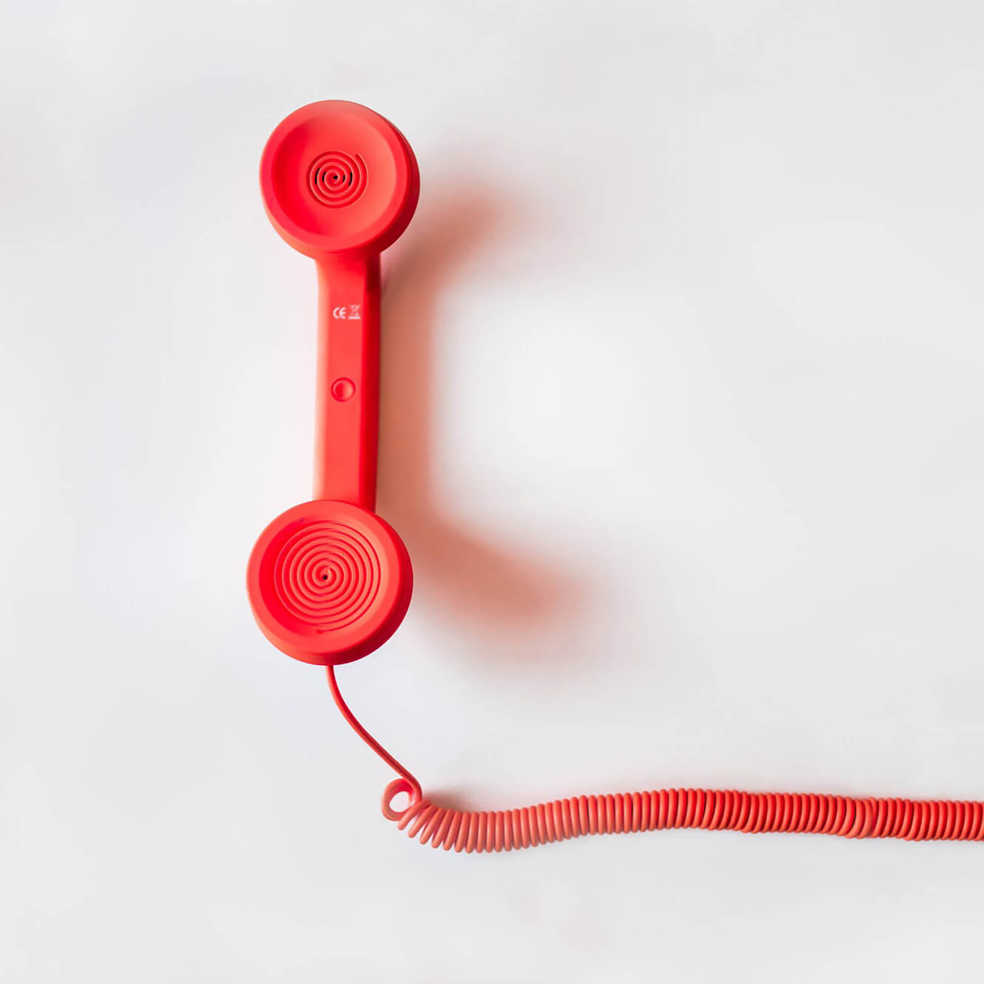Red telephone against a white background.