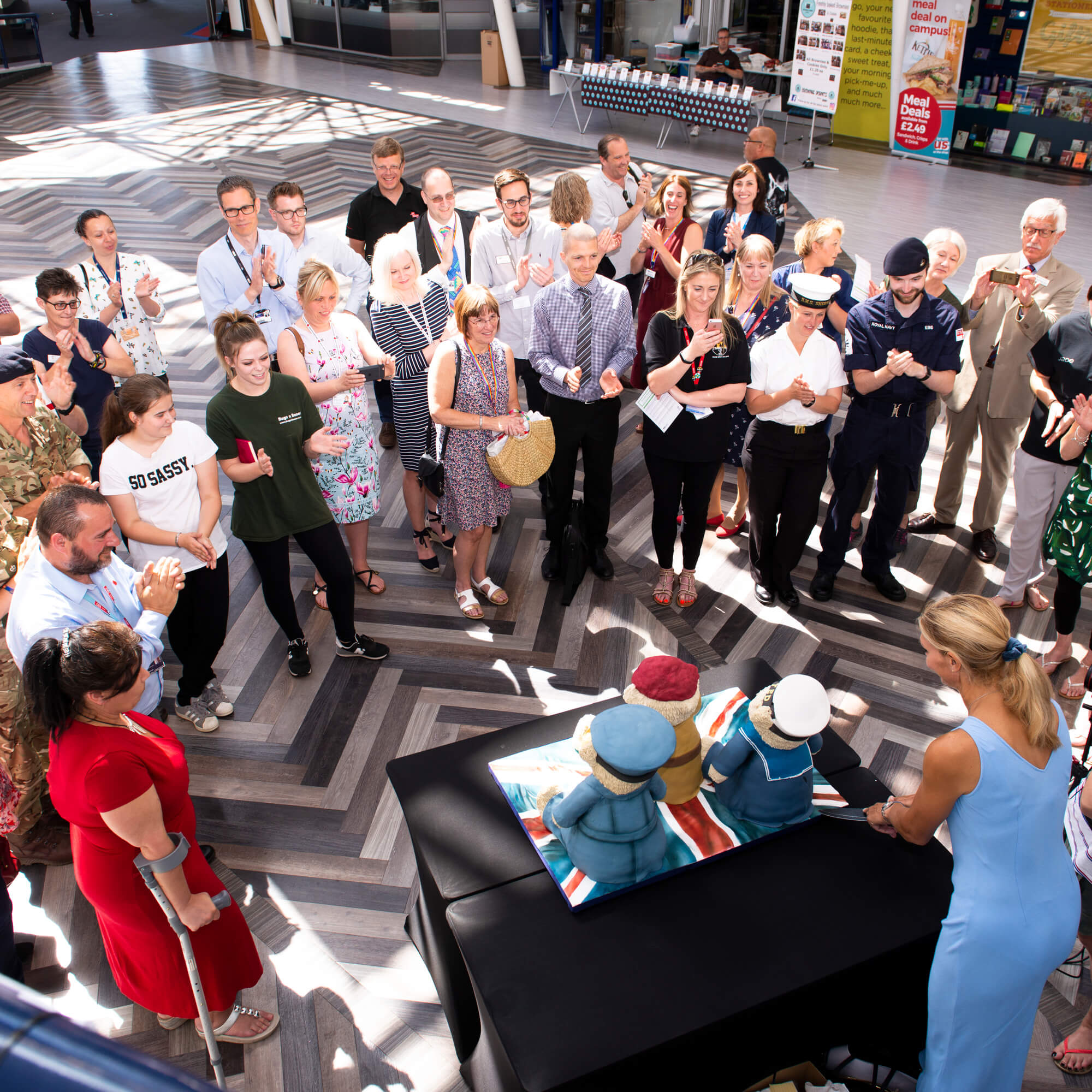 A group of people standing during the family forces event in the University's atrium