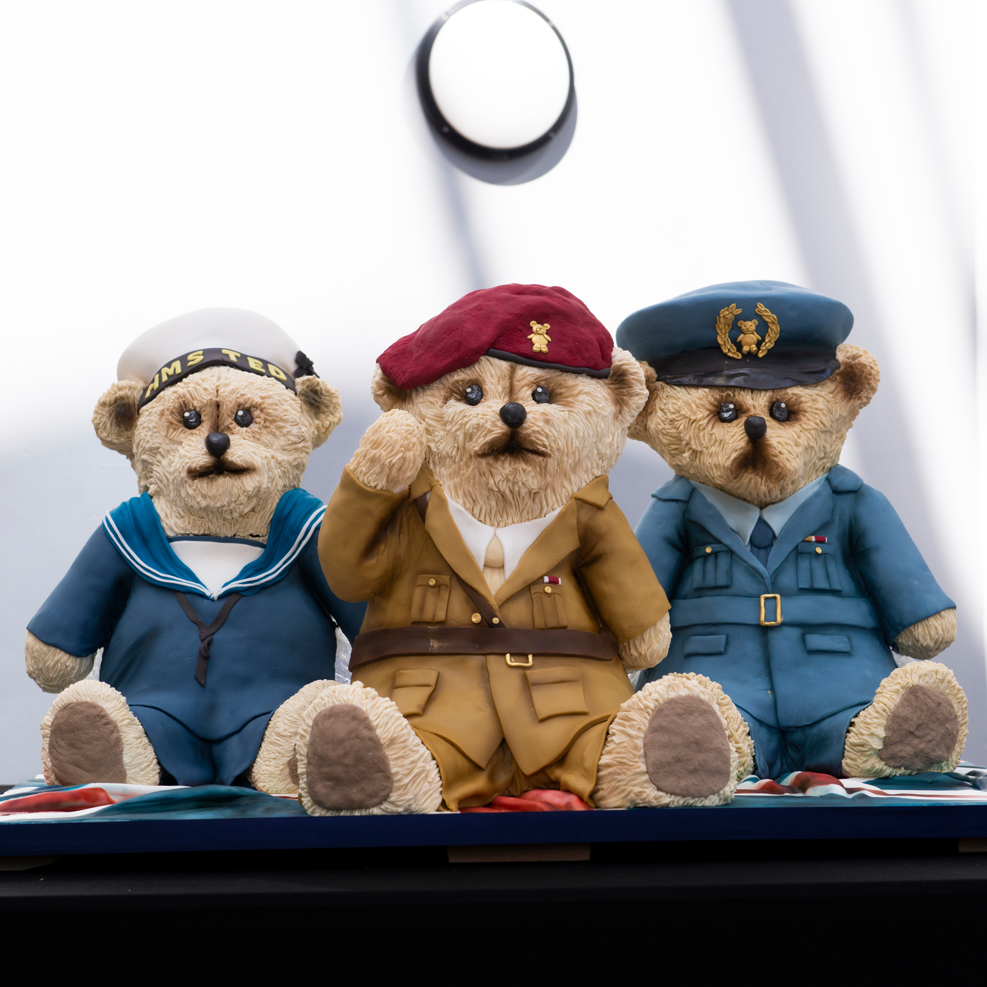 Three armed forces teddies sat next to each other on a table.