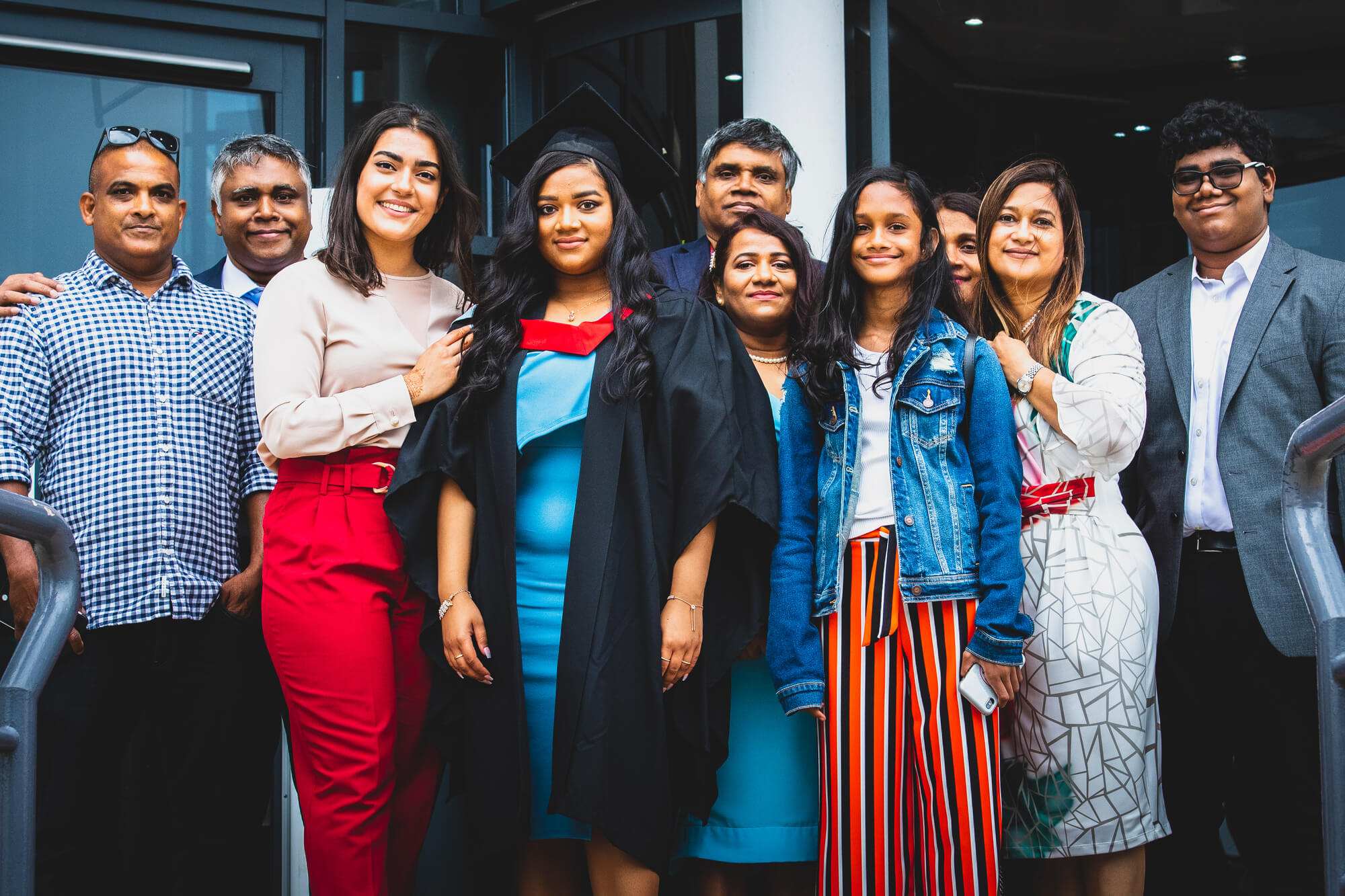 A student stood with a large family at a graduation ceremony