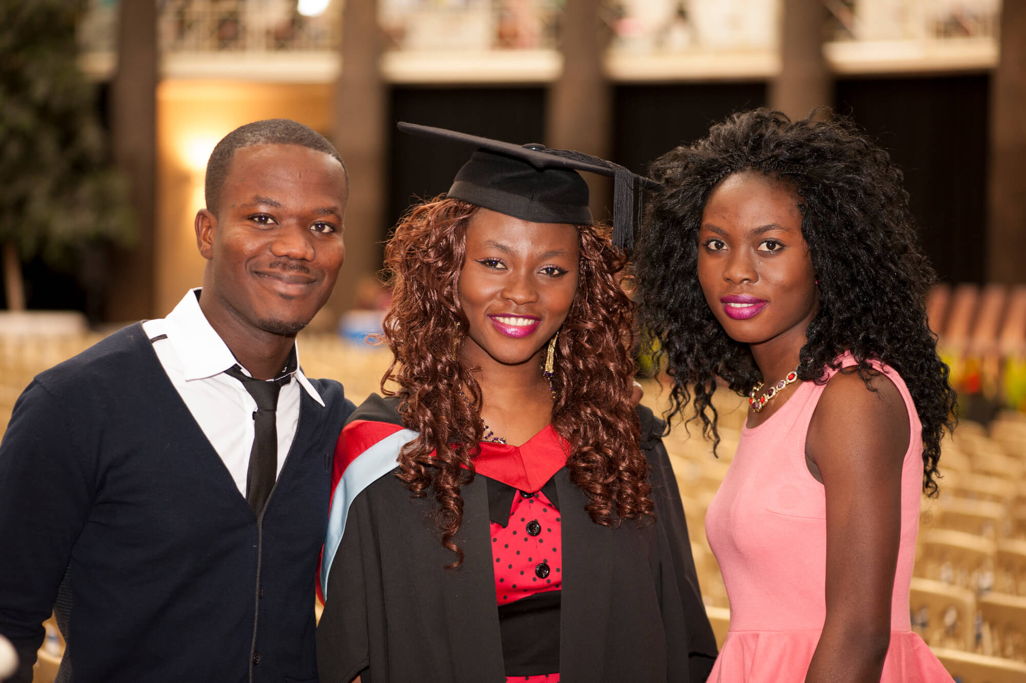 A student in a graduation cap and gown with two family members.