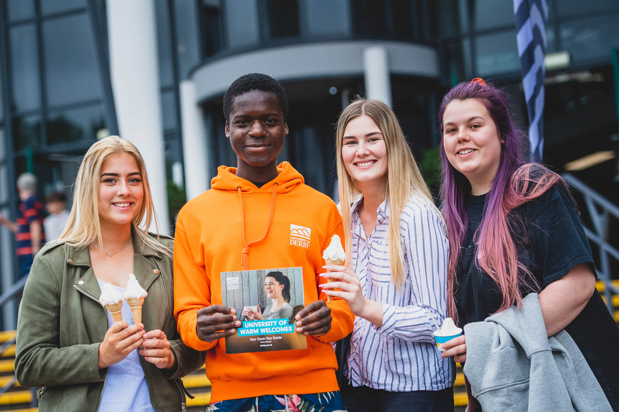 Three prospective students holding ice creams with a Student Ambassador outside the University.