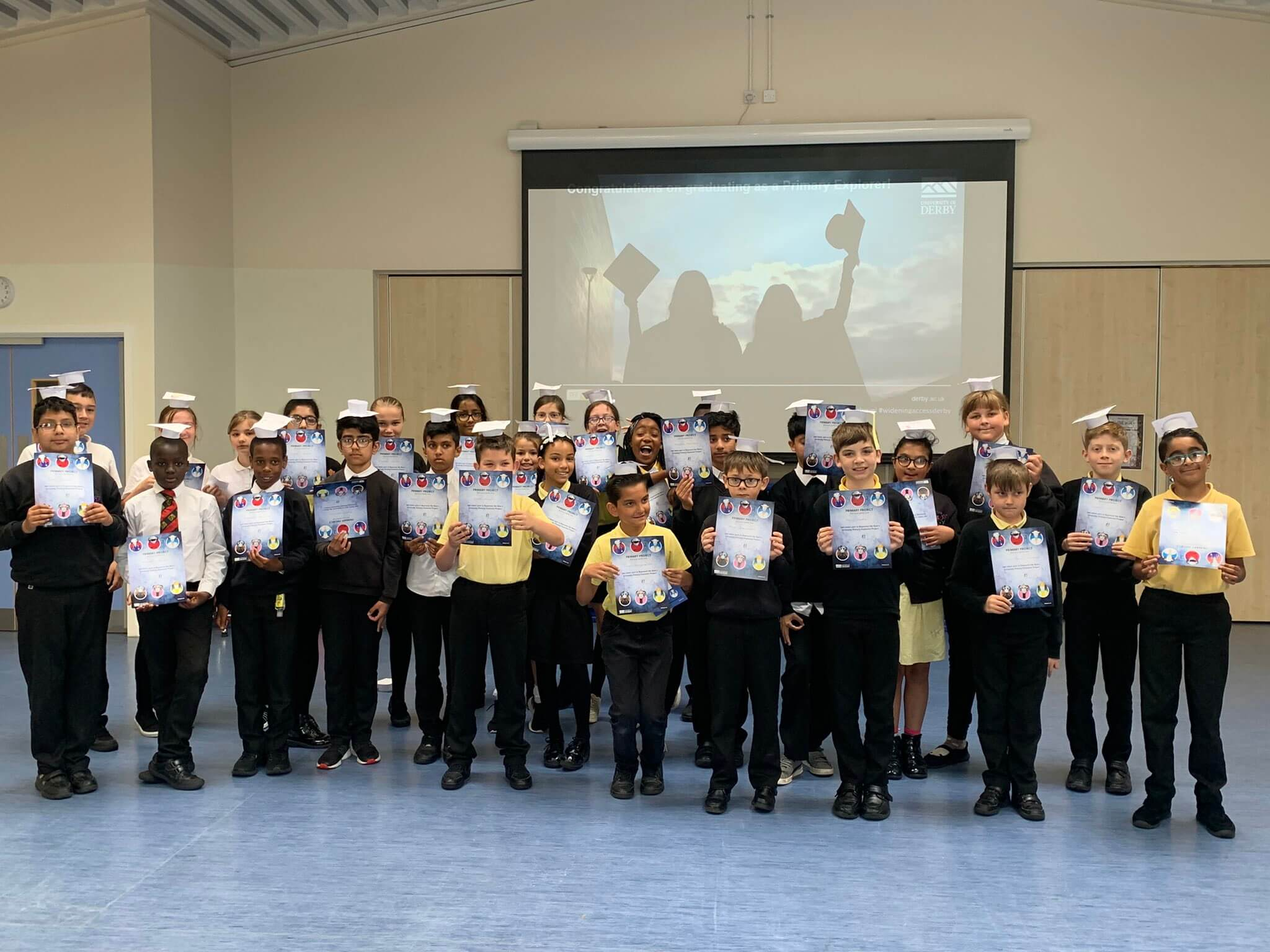 Year 6 students at Bemrose Primary holding their graduation certificates and hats.