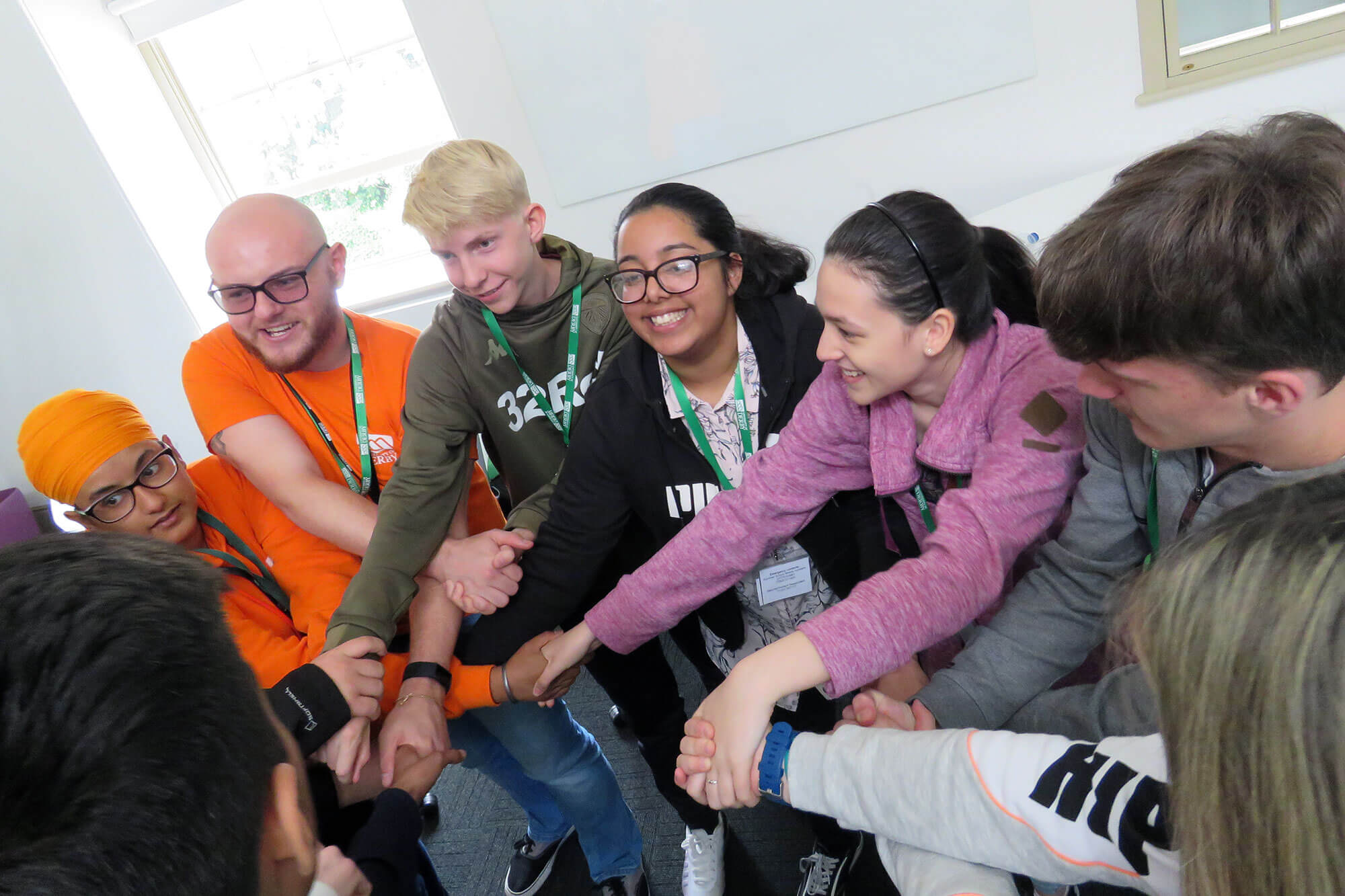 Students and Student Ambassadors standing in a circle and interlocking hands at Summer School 2019