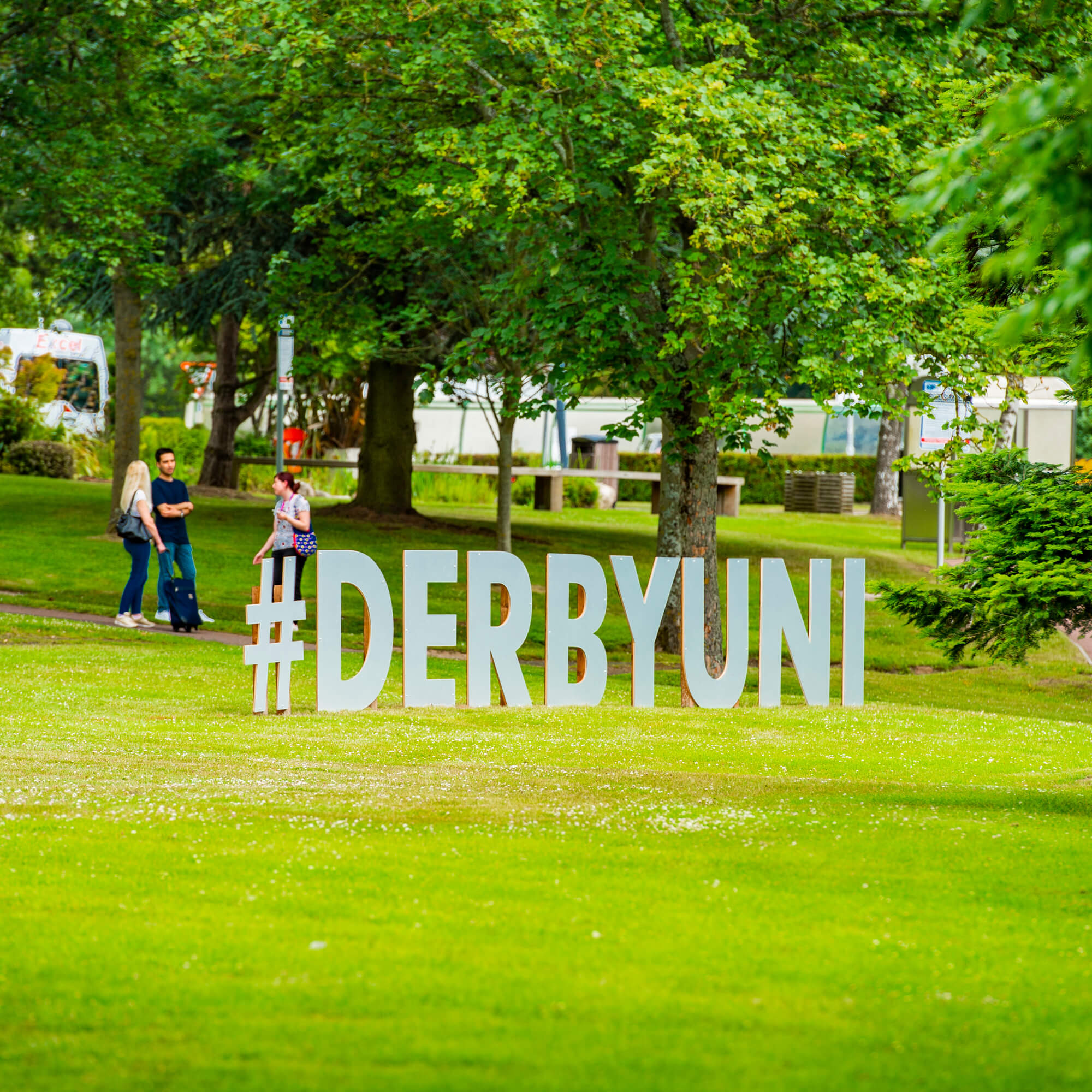 The #derbyuni sign on the grass in front of the University.