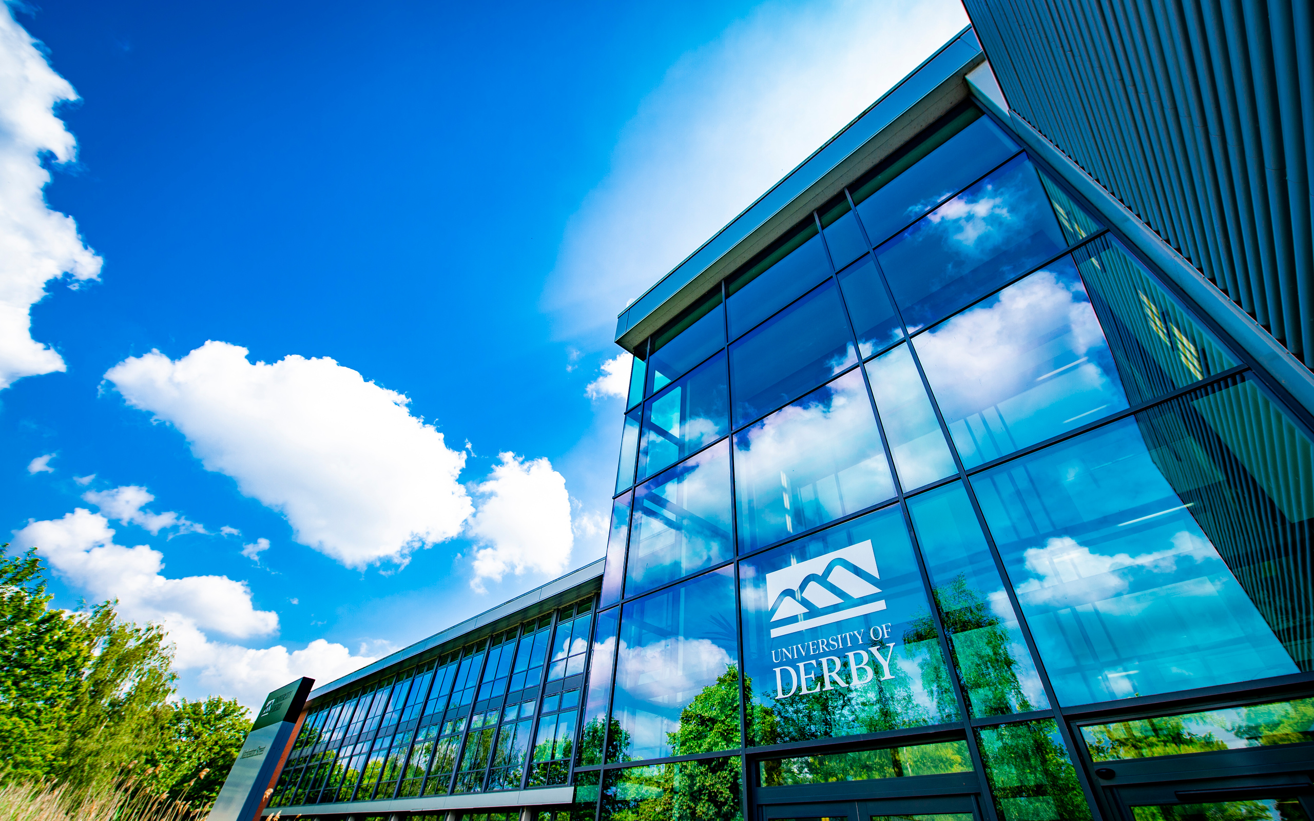 A reflection of the trees on the University of Derby's Markeaton Street building.