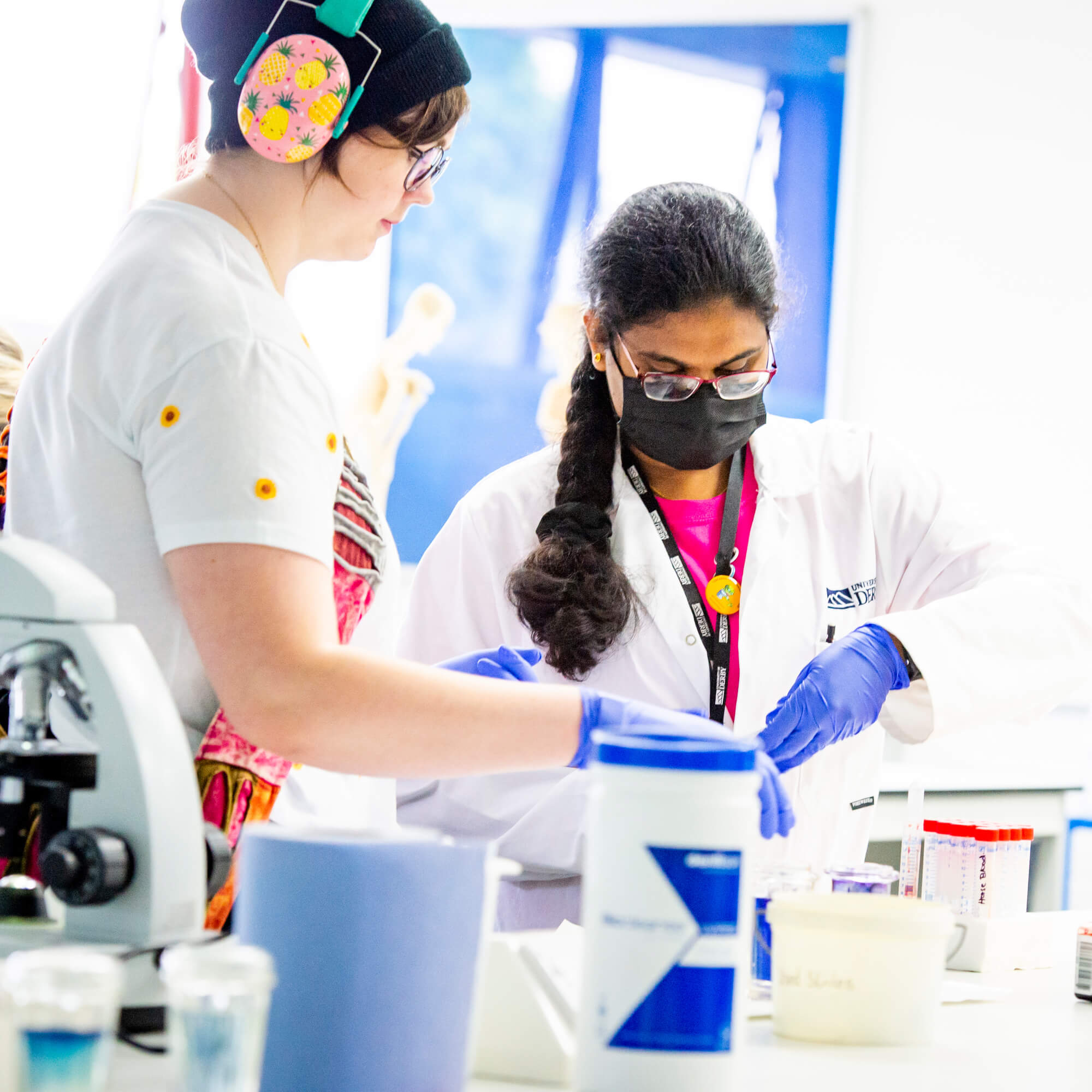 A student pouring liquids in a science lab with a parent.