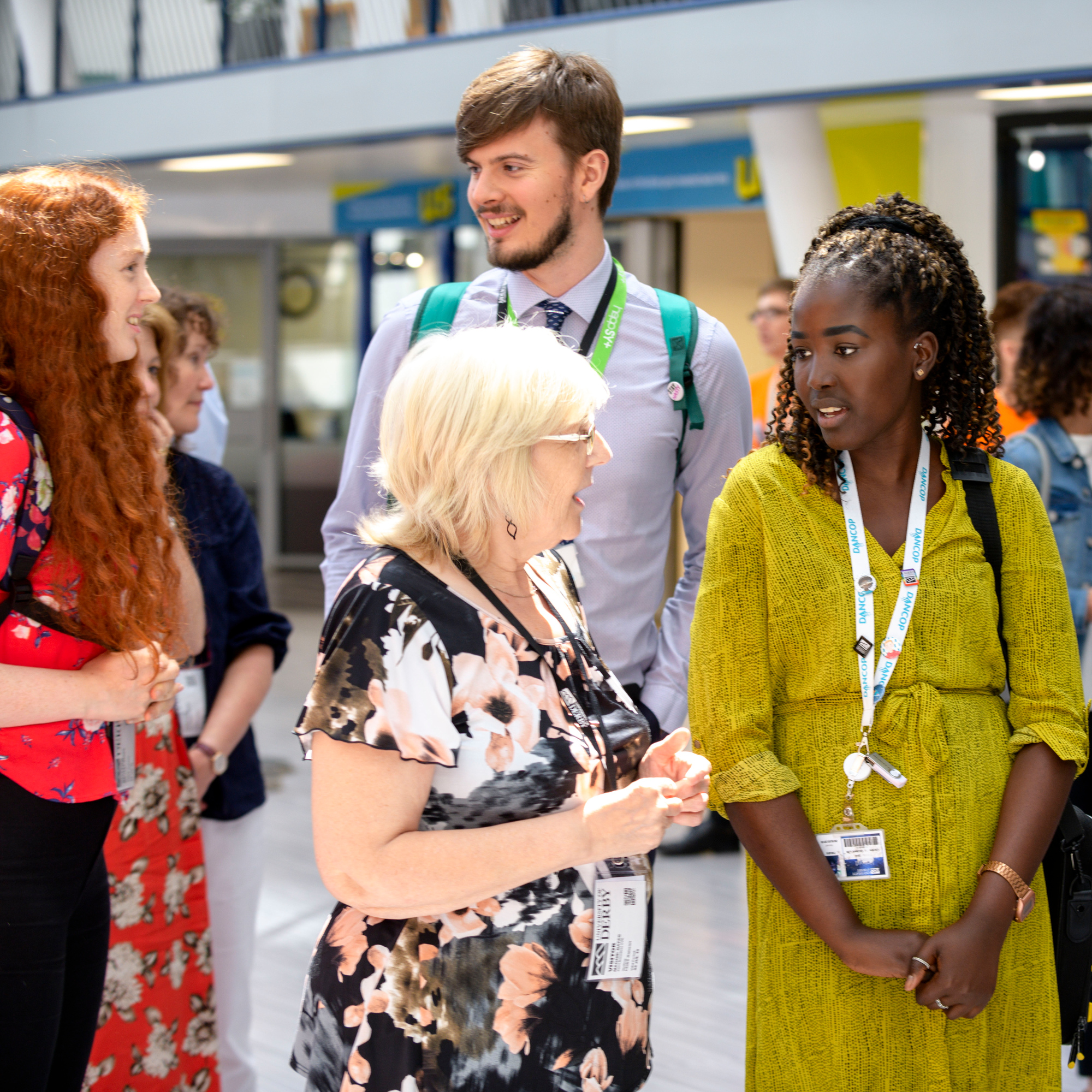 A careers advisors speaks to a University staff member with two people in the background of the Atrium.