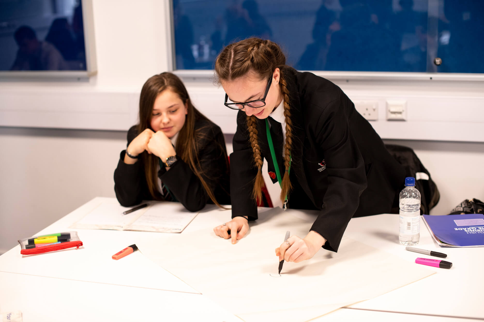 Two students working on an activity at a table with one student writing.