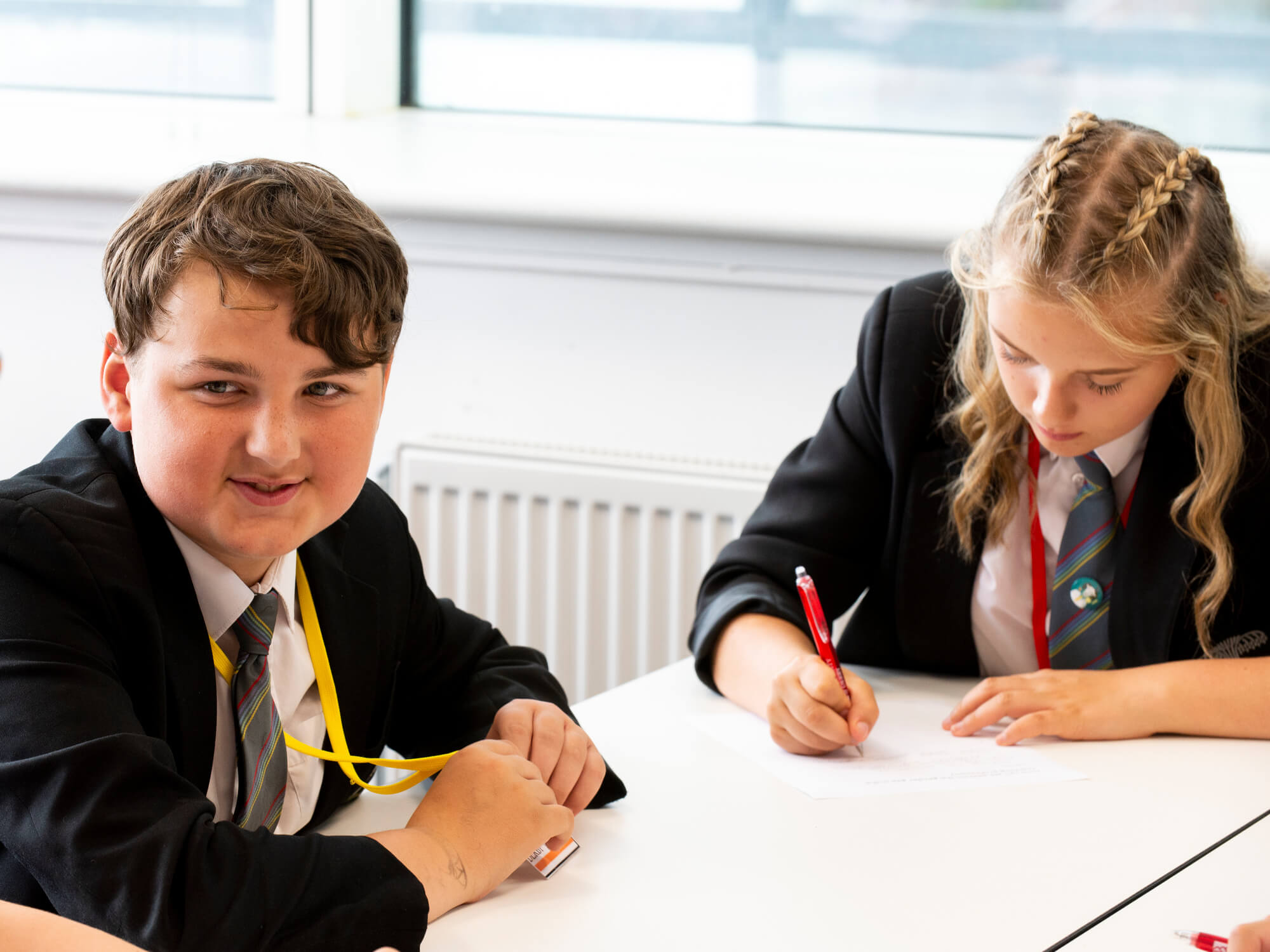 Two students around a table completing an activity.