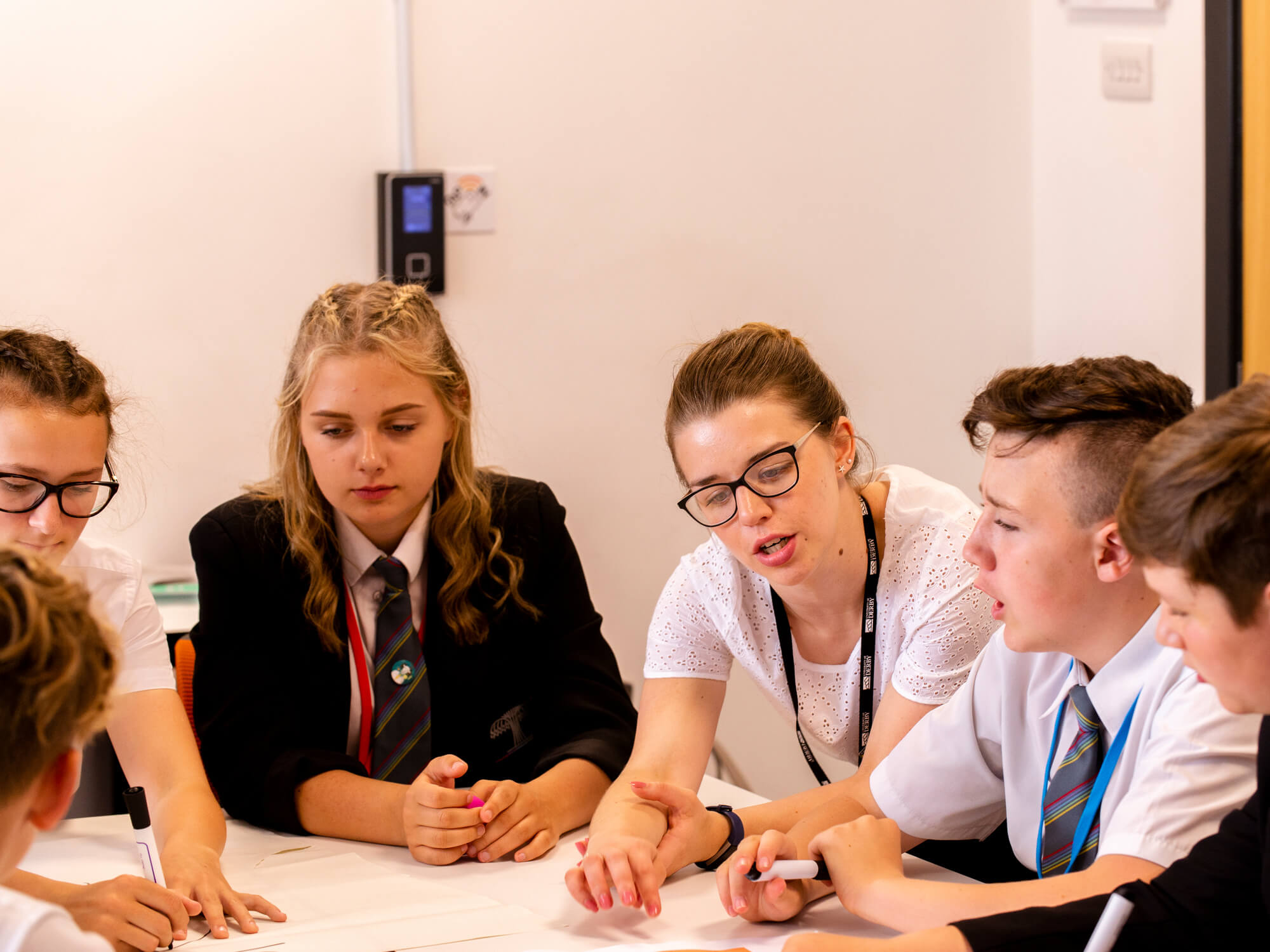 Students sitting round a table engaging in class discussions with the teacher.
