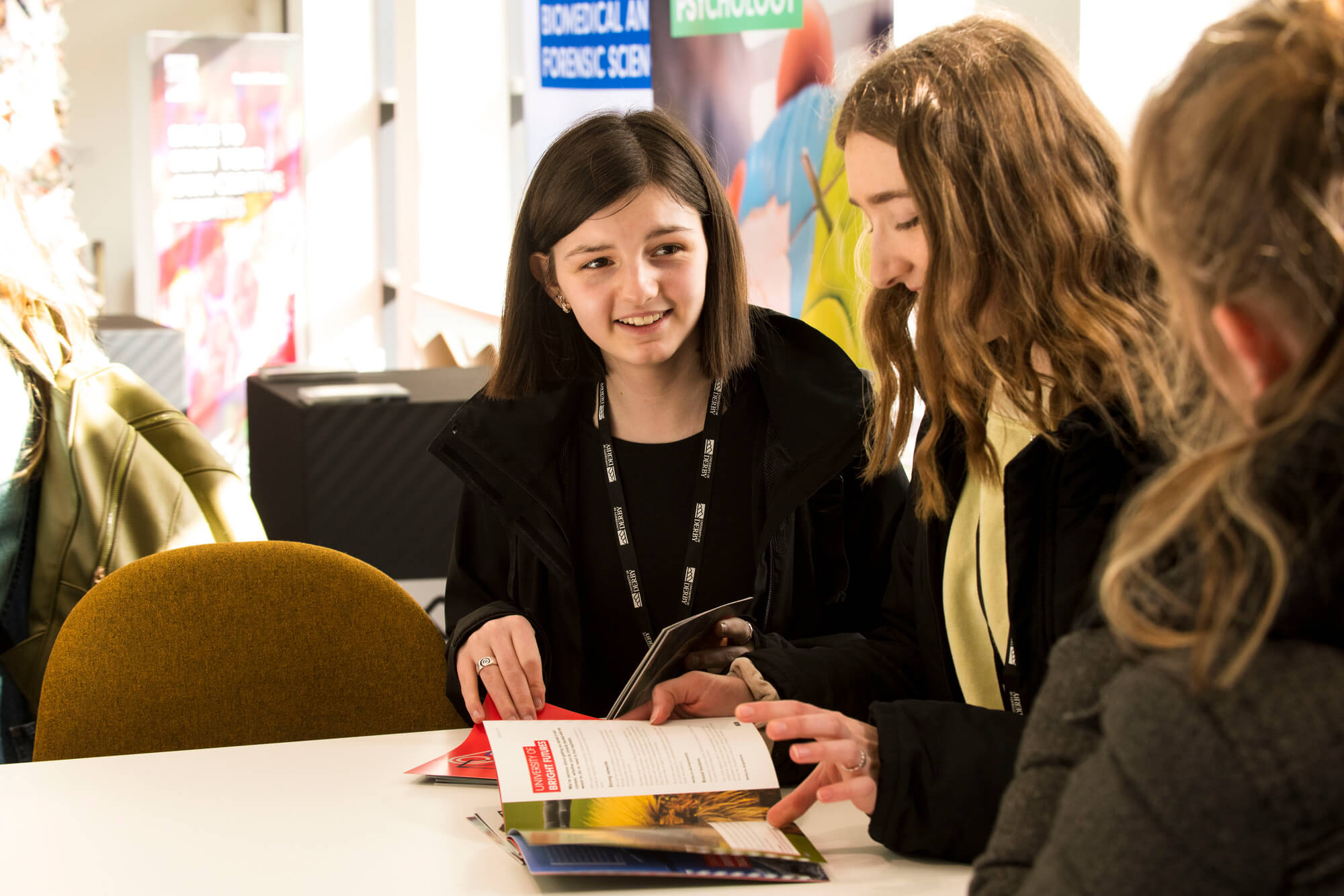 Two students sat reading a prospectus at STEMFest.