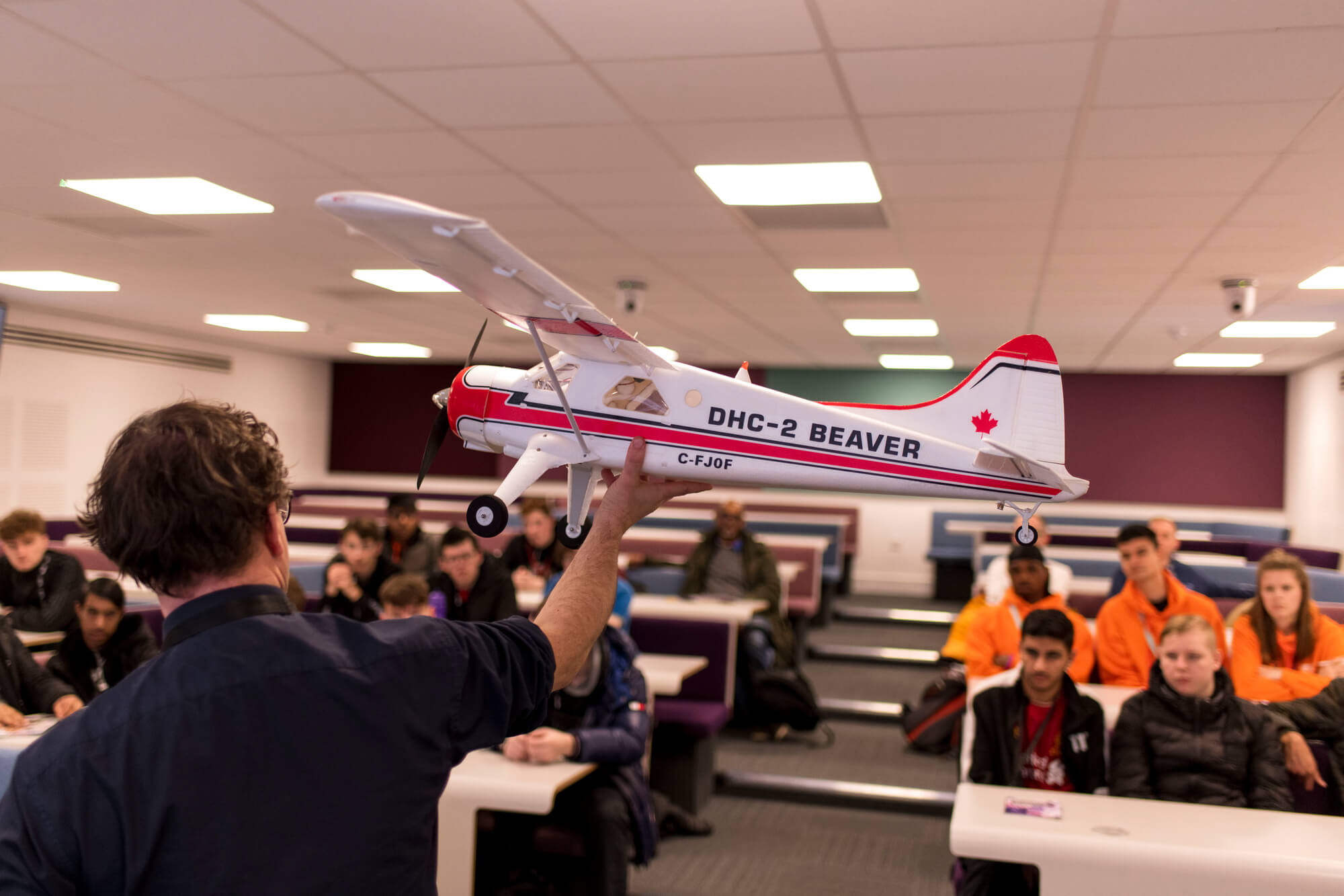 A lecturer holding a model plane in front of a lecture theatre of students.