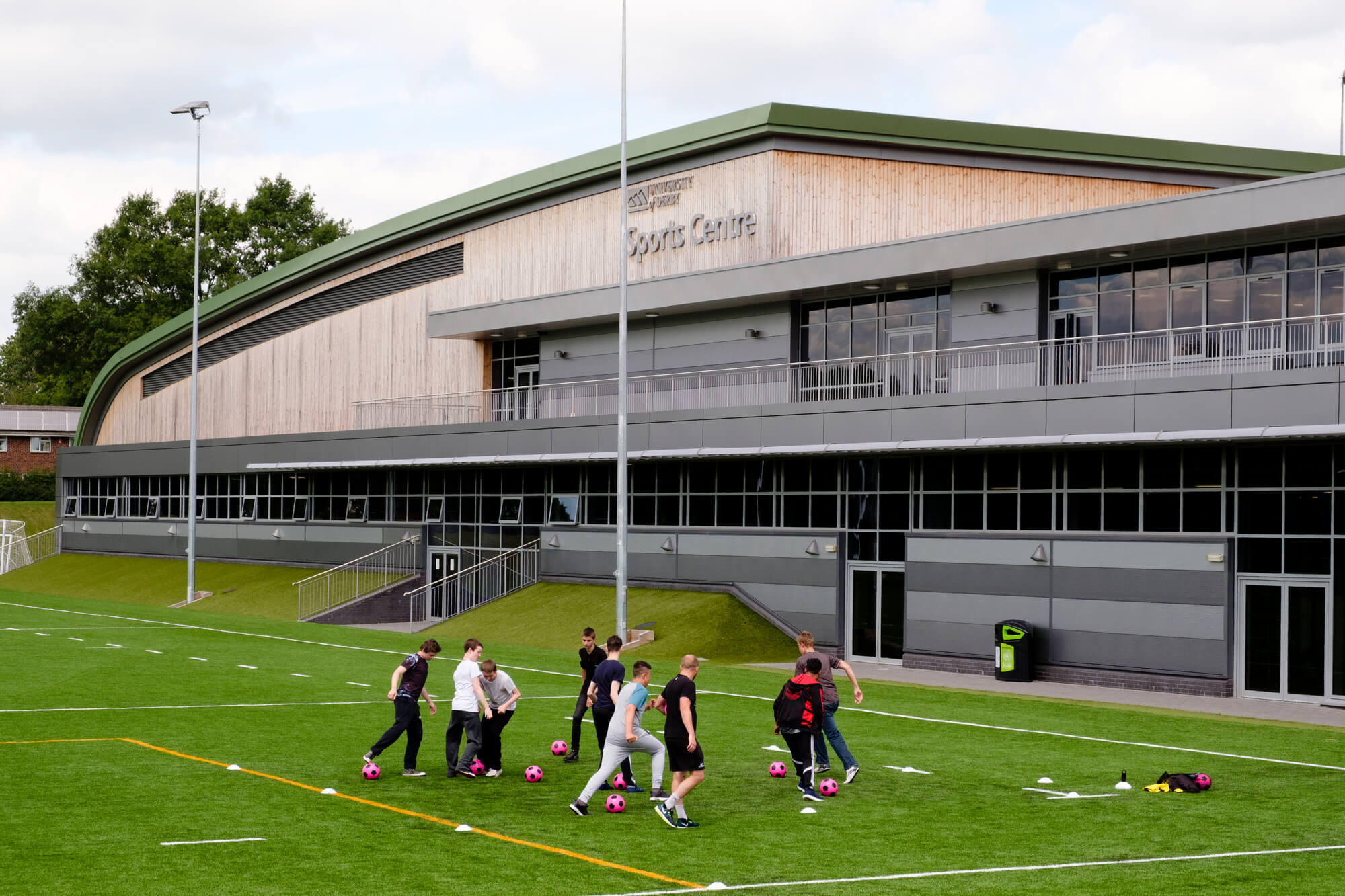 Students learning football skills with the University of Derby's sport centre in the background.
