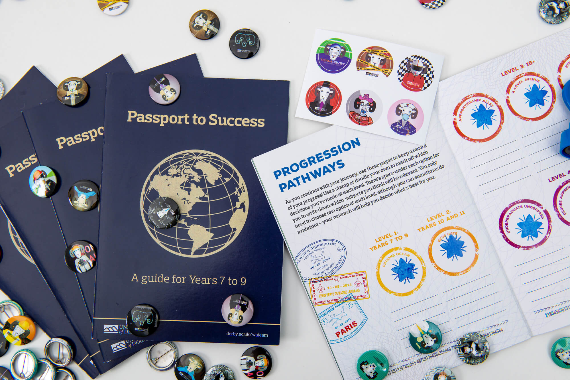 An open progression pathways booklet on a table surrounded by badges