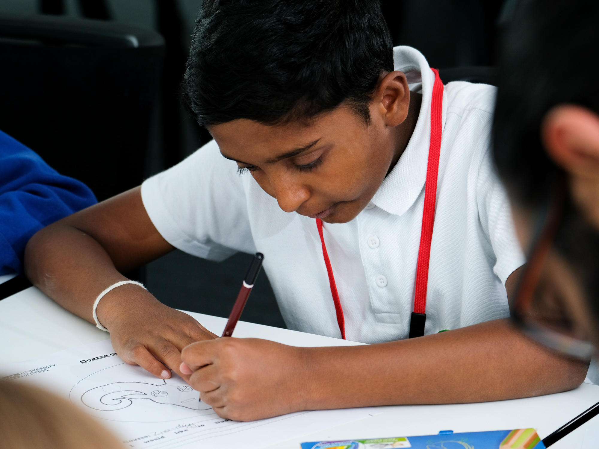 A primary school aged student colouring in a picture in a classroom.