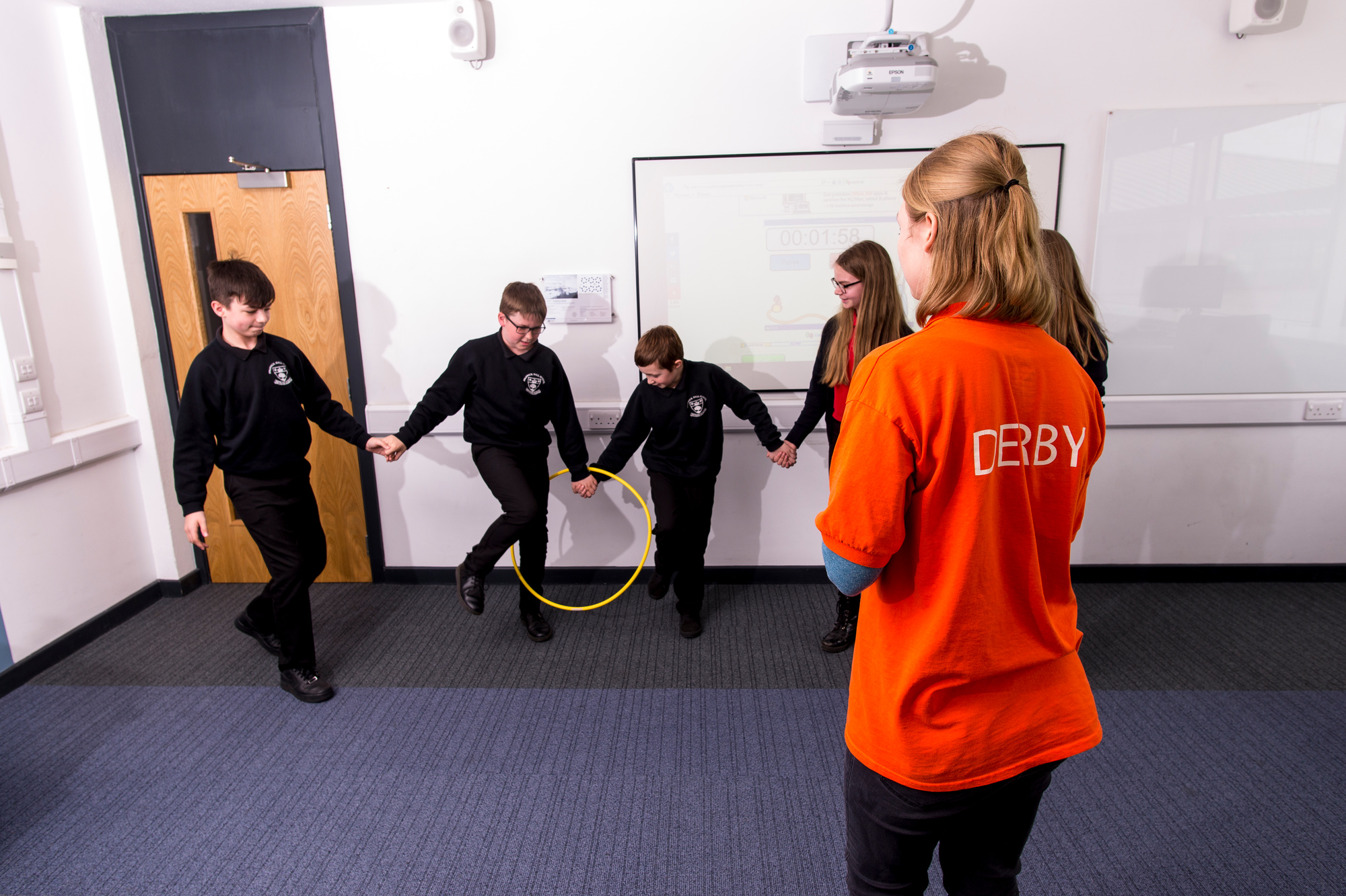 5 students trying to pass a hoop along a line with a Student Ambassador.
