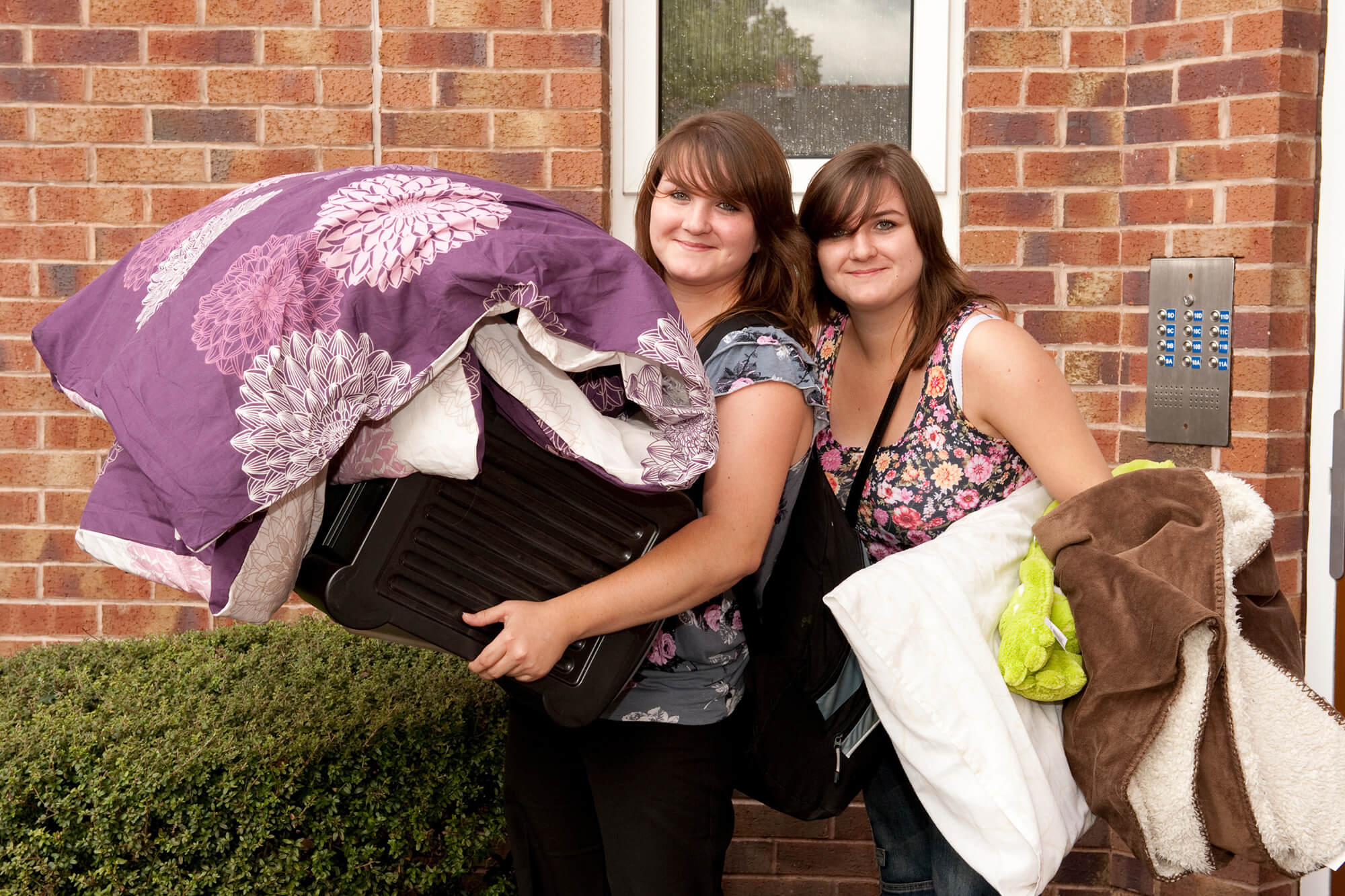 Two people holding quilts and pillows getting ready to move into new accommodation