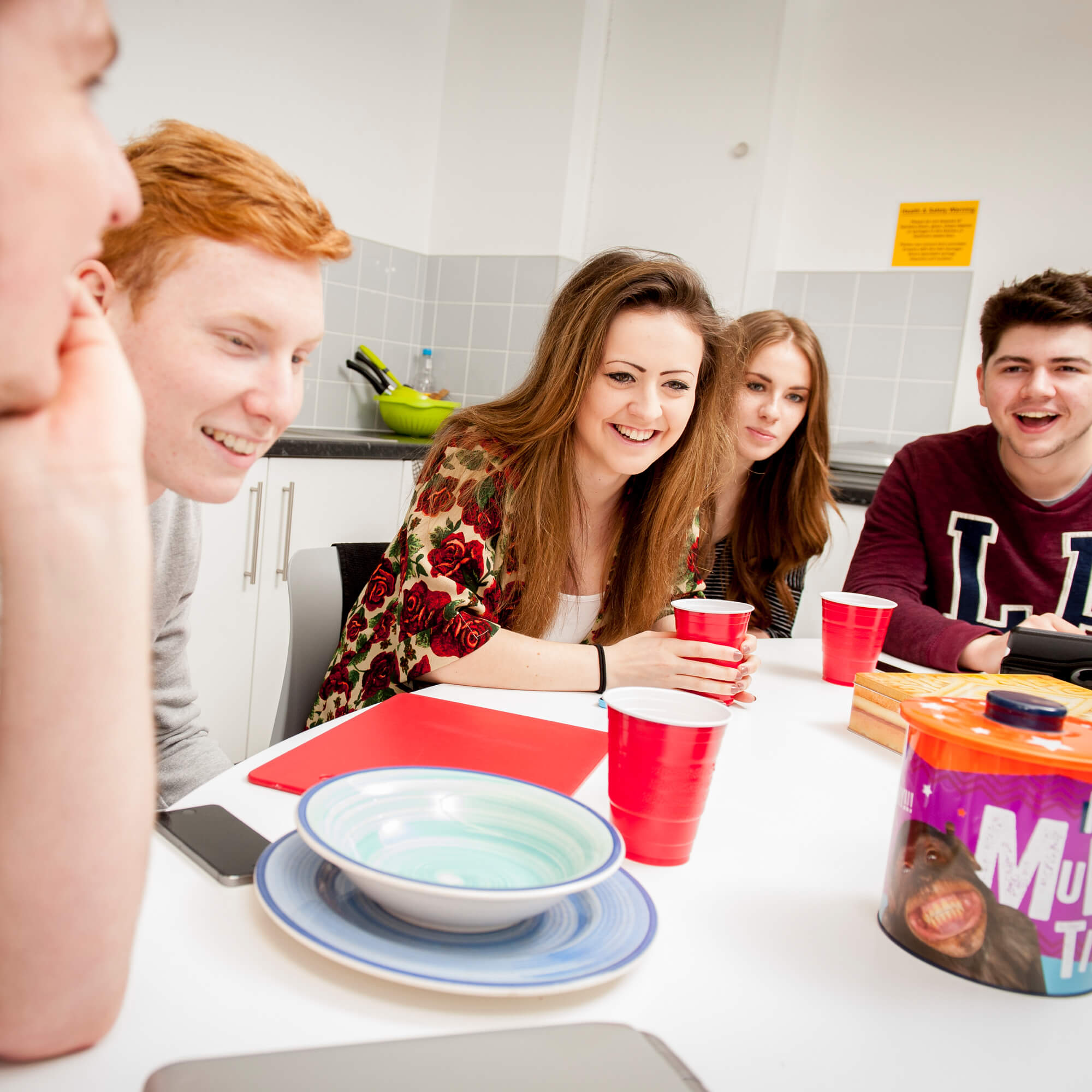 Five students sitting round a table in halls of residence