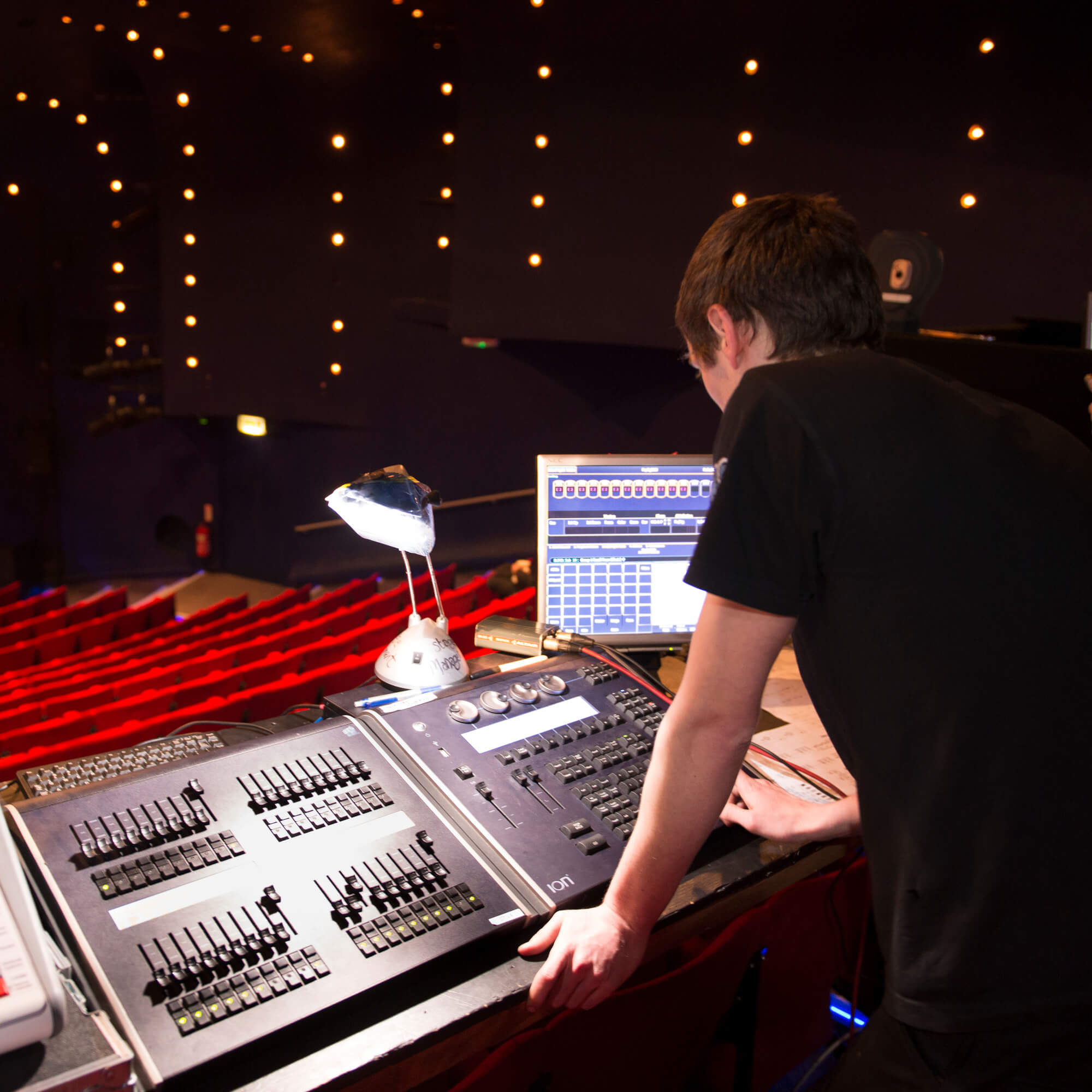 A technical theatre student works on sound equipment in the theatre