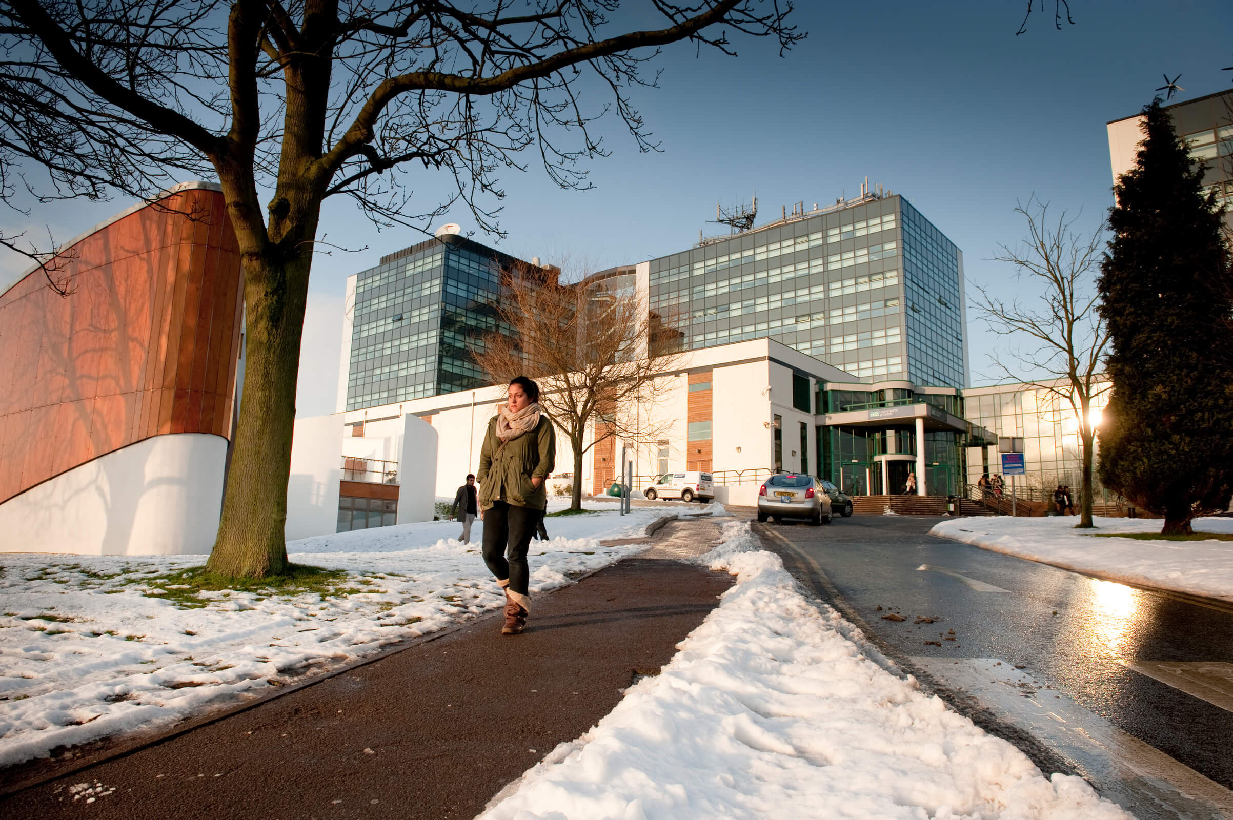 A student walking away from Kedleston Road campus in the snow
