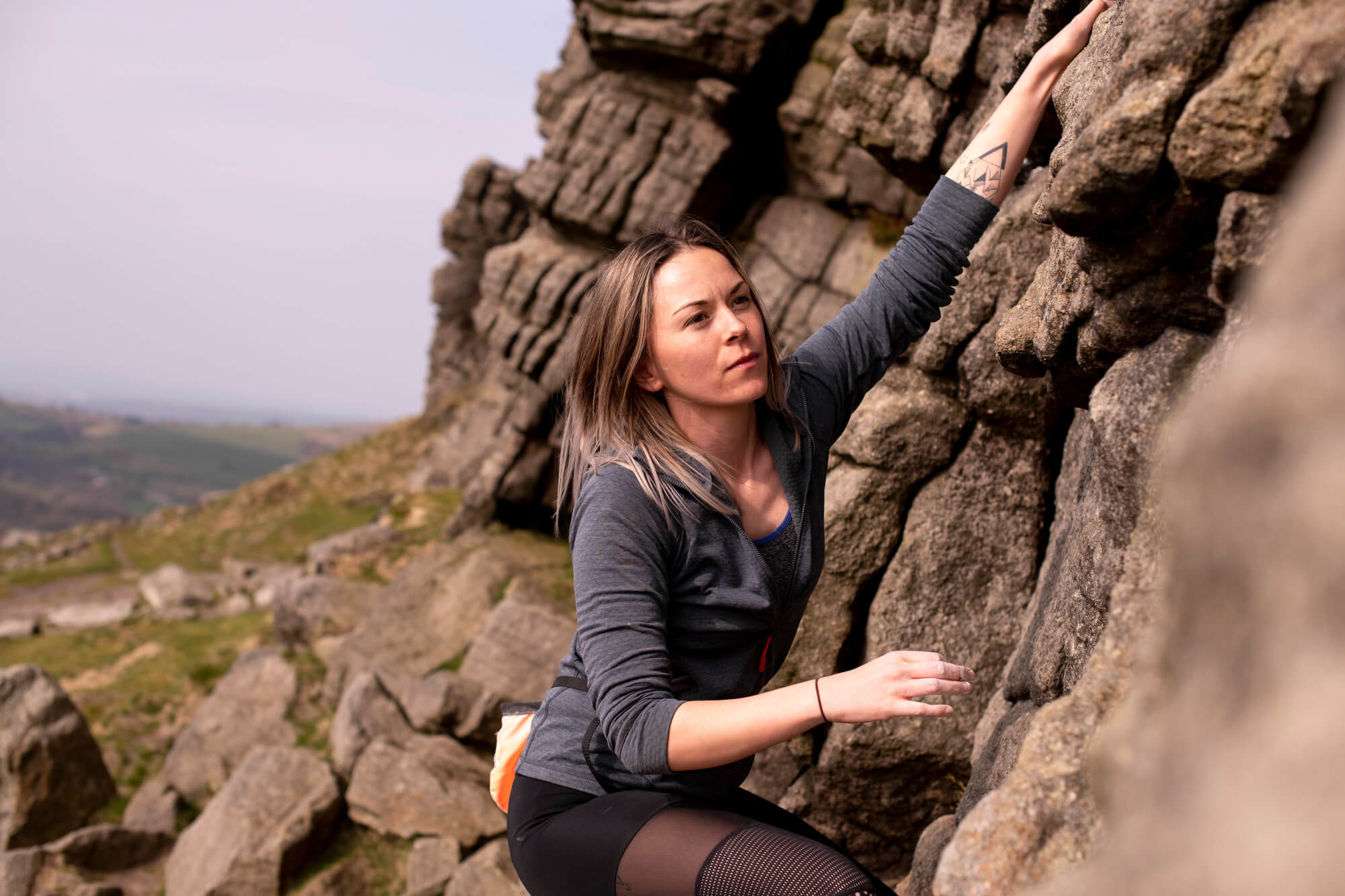A University of Derby Outdoor student climbs rocks concentrating on her next move