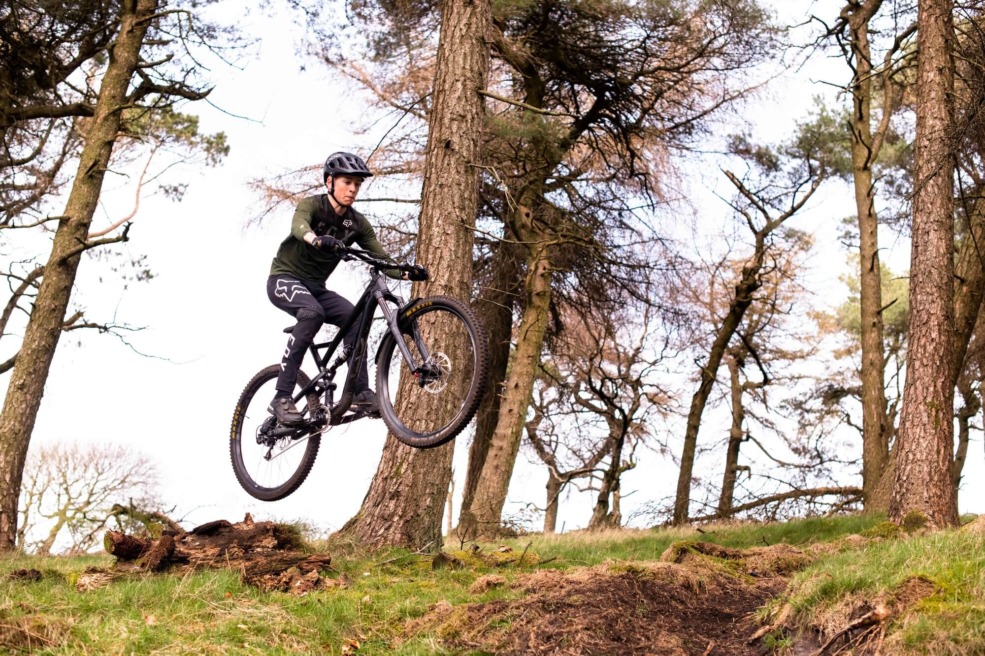 A University of Derby Outdoor student flies through the air on a mountain bike scaling grassy terrain and trees